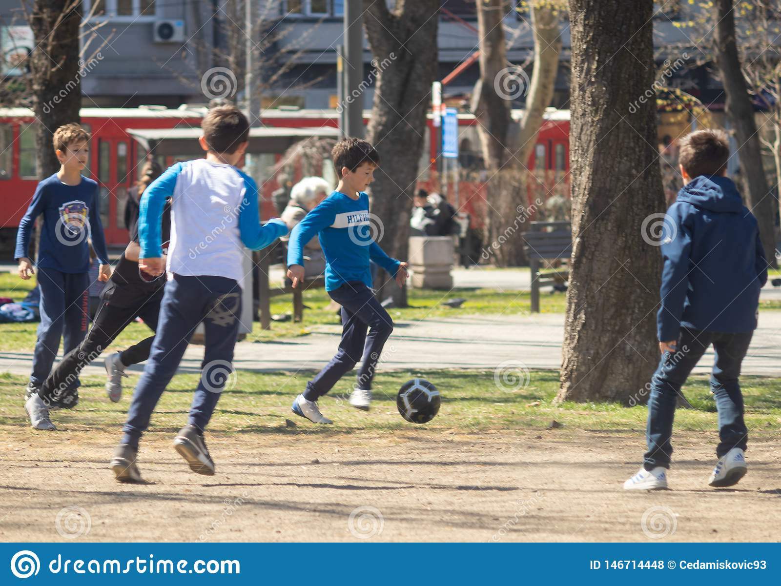 Ungar som spelar fotboll i, parkerar på en solig dag