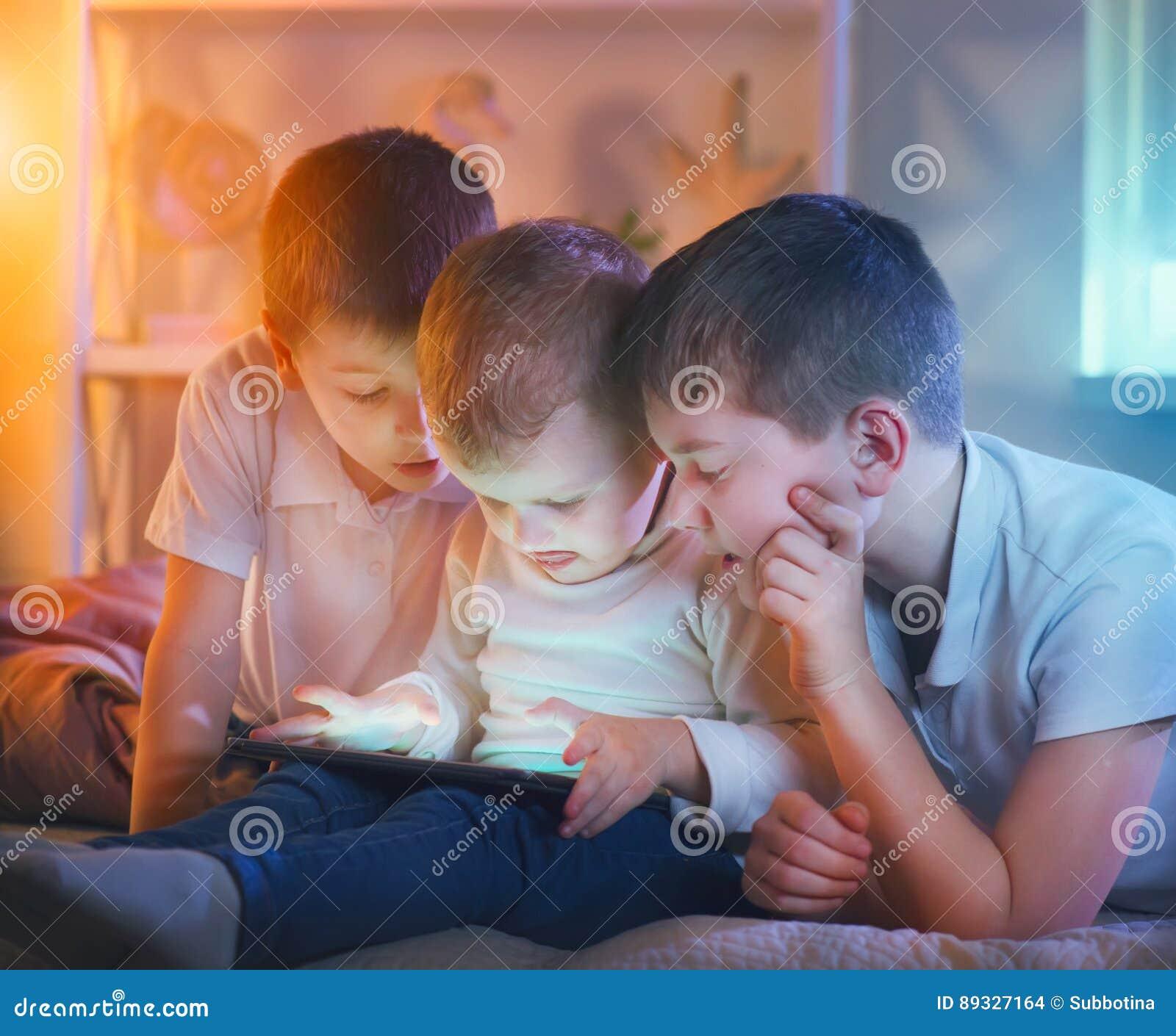 Ungar som spelar lekar på minnestavlaPC Tre pyser med minnestavladatoren