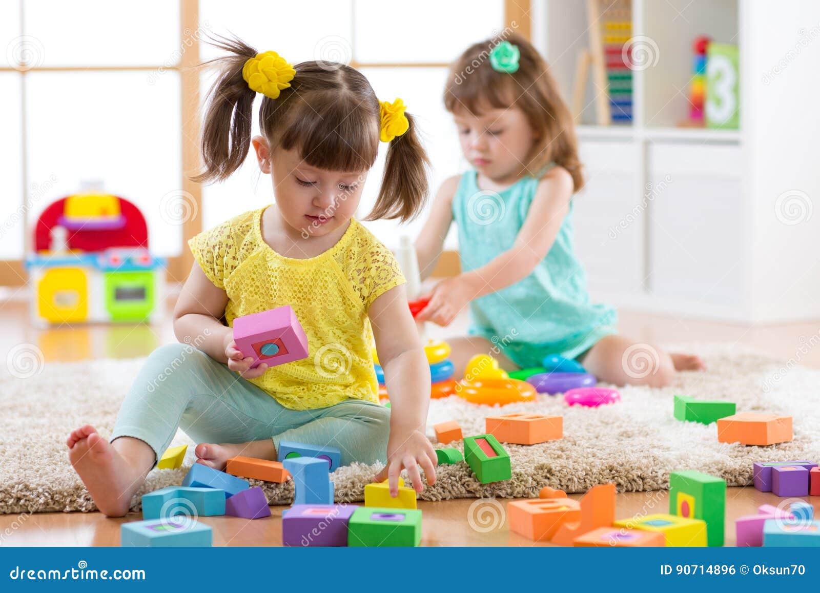 Ungar som spelar med färgrika kvarterleksaker Barn som hemma bygger torn eller daycaremitten Bildande barnleksaker för den förträ
