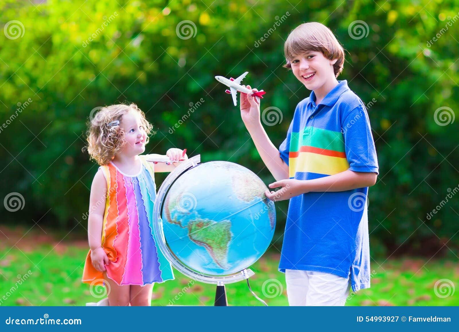 Ungar som spelar med flygplan och jordklotet