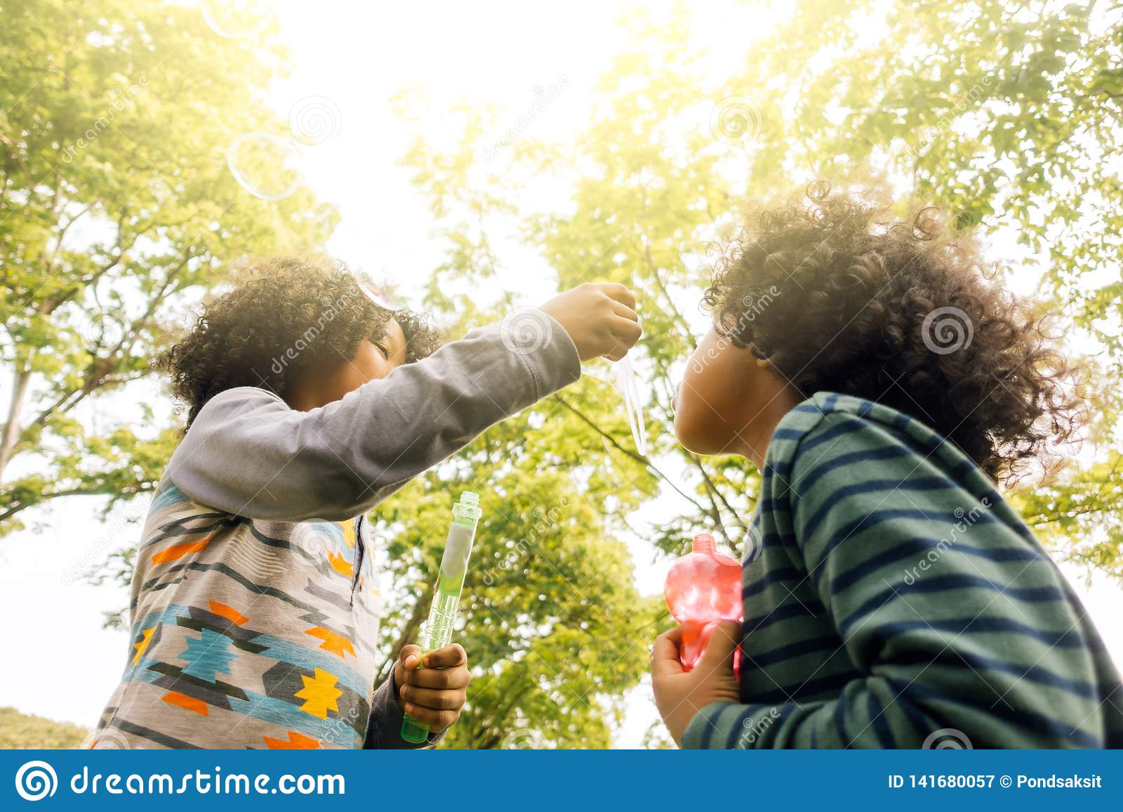 Ungar som spelar med vänner Ungar som spelar blåsa bubblor