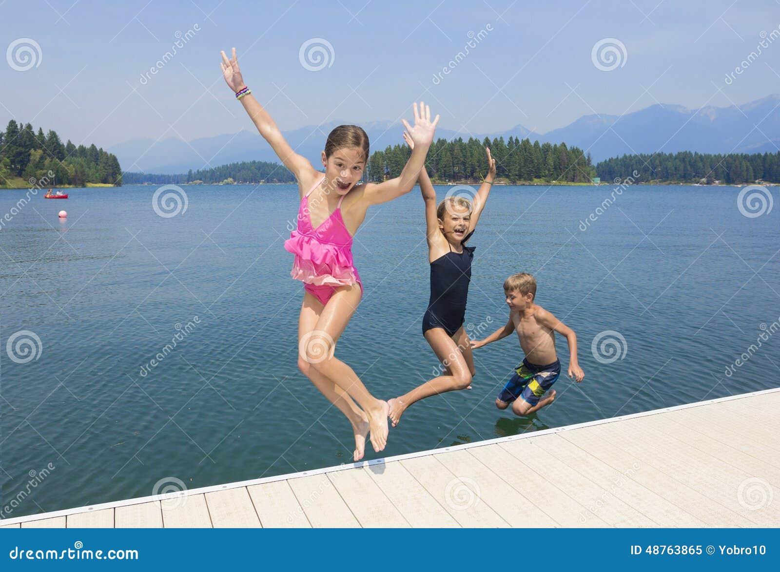 Ungar som spelar på sjön på deras sommarsemester