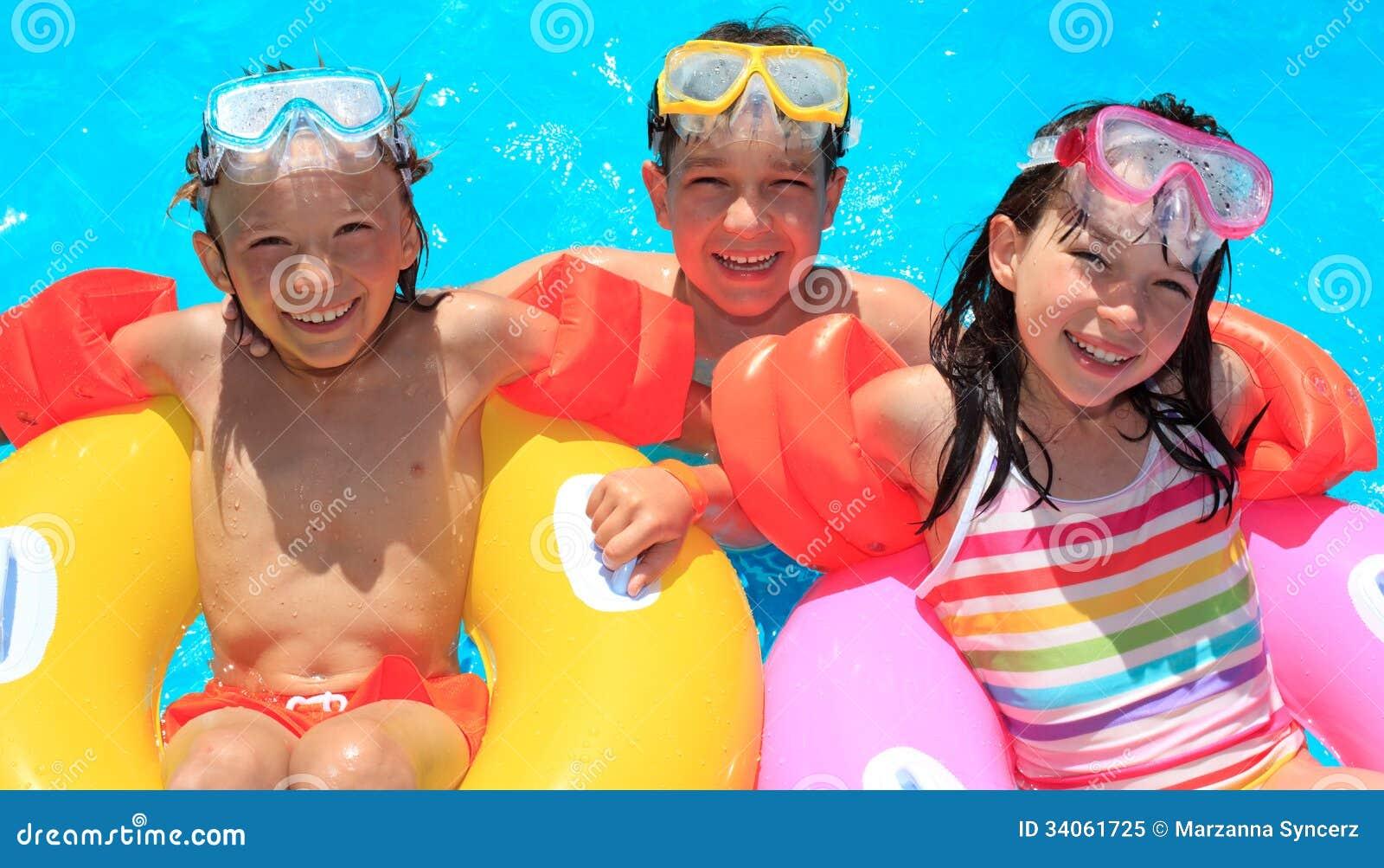 Ungar som svävar i simbassäng