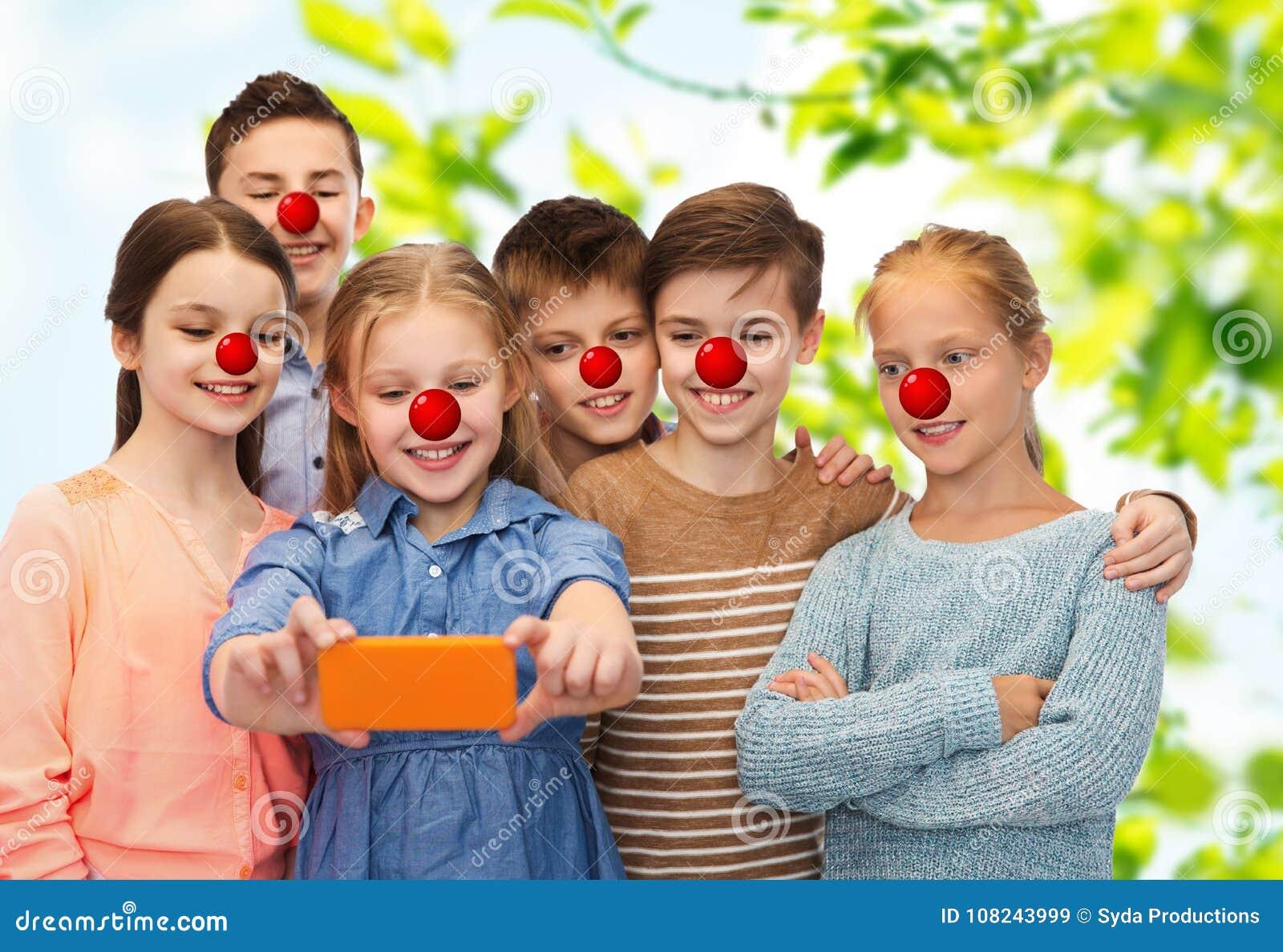 Ungar som tar selfie med smartphonen på den röda näsdagen