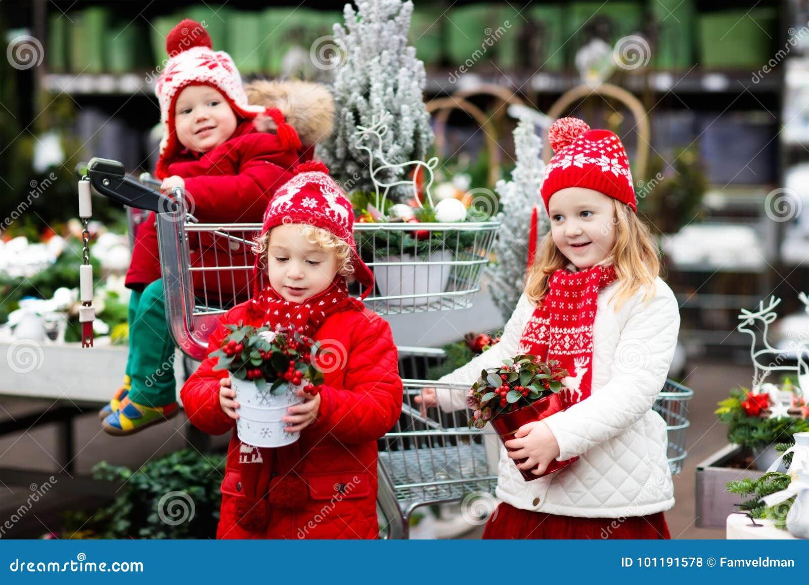 Ungar som väljer julgranen Shoppa för Xmas-gåvor