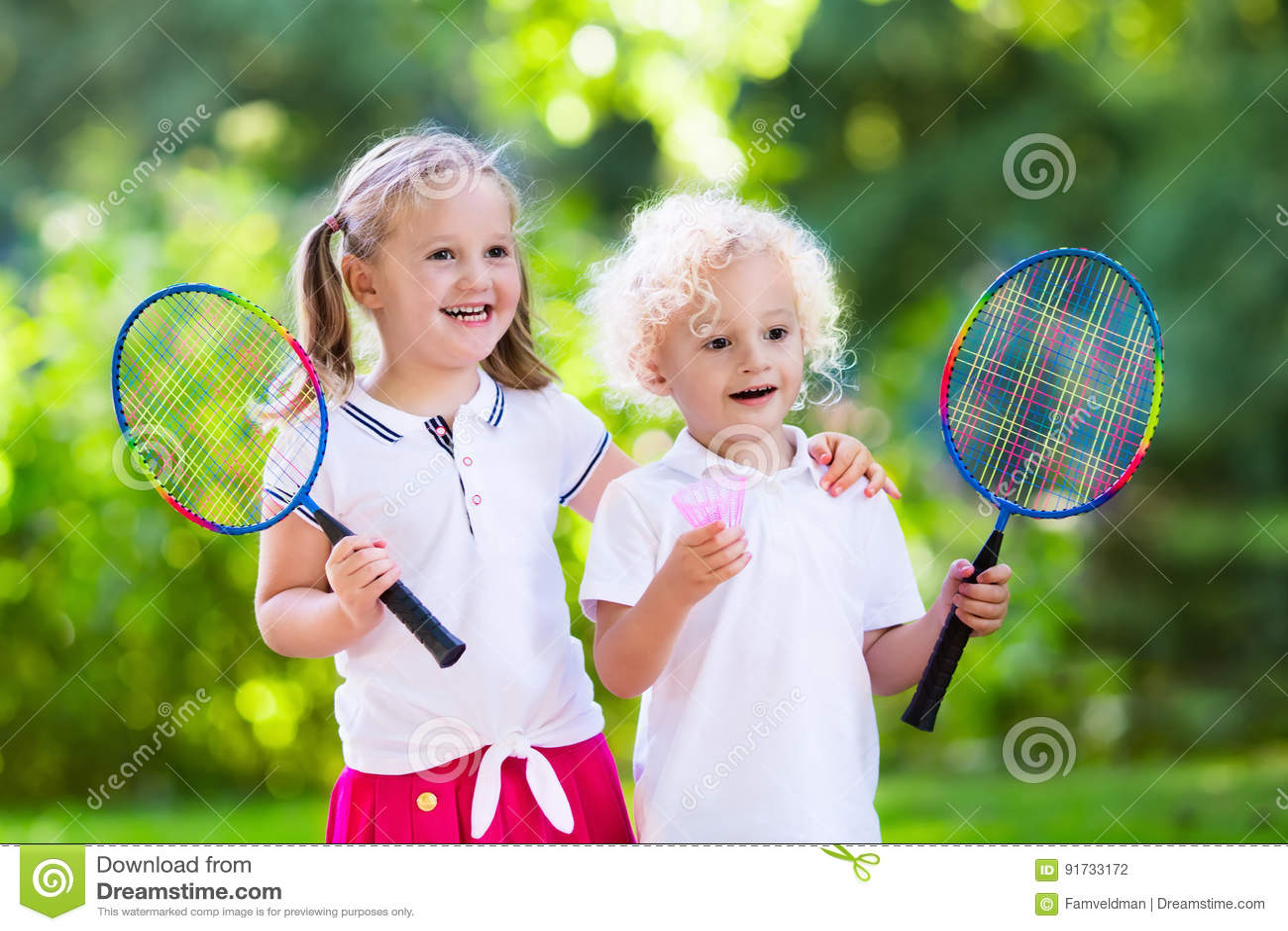 Ungar spelar badminton eller tennis i utomhus- domstol