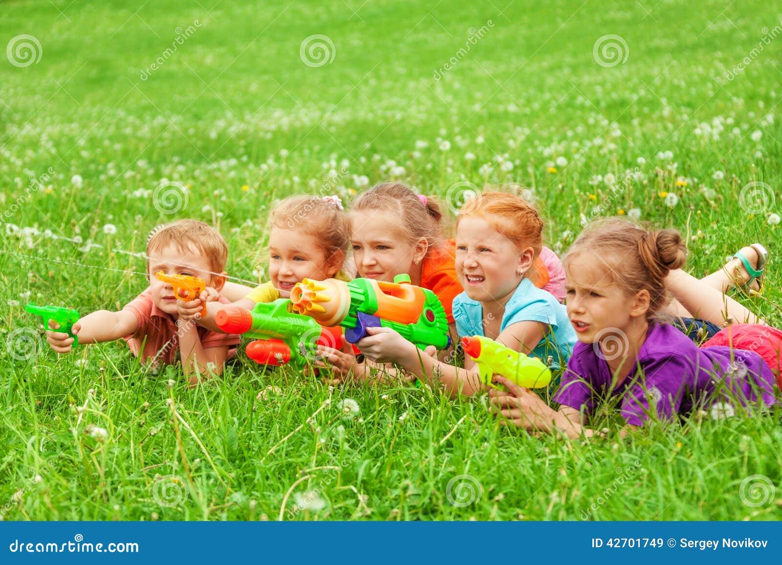 Ungar spelar med vattenvapen som lägger på en äng