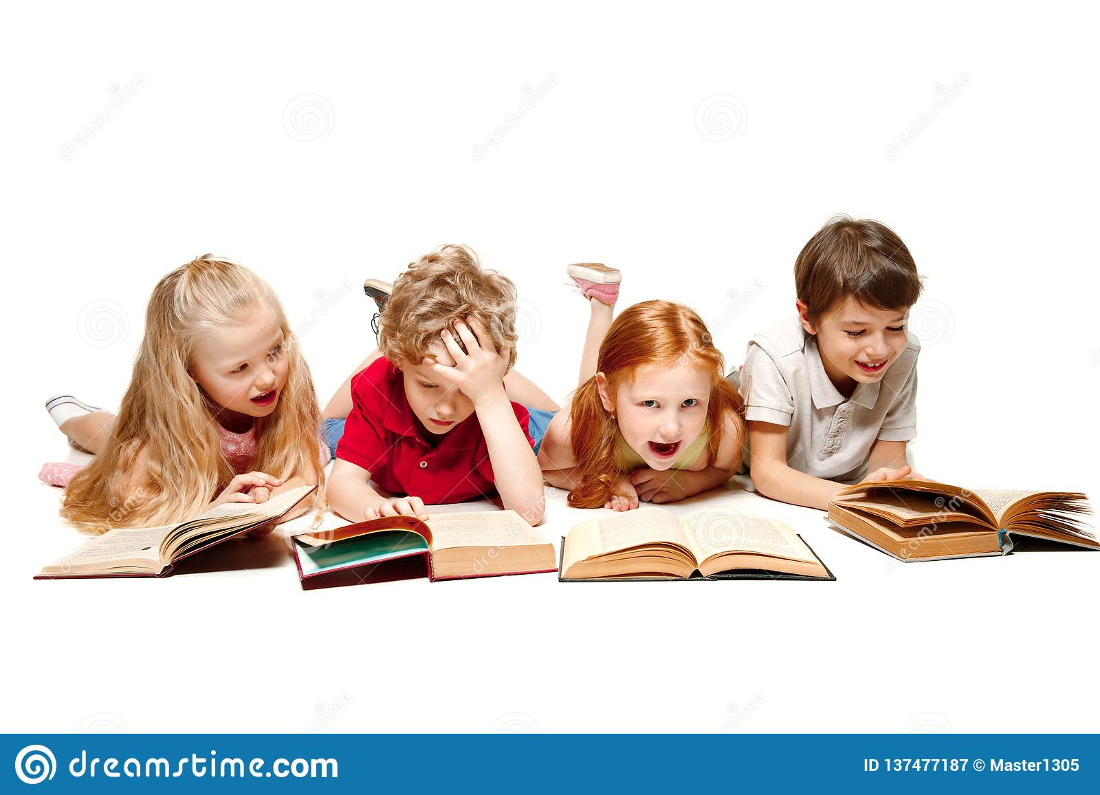 Ungarna pojke och flickor som lägger med böcker som isoleras på vit