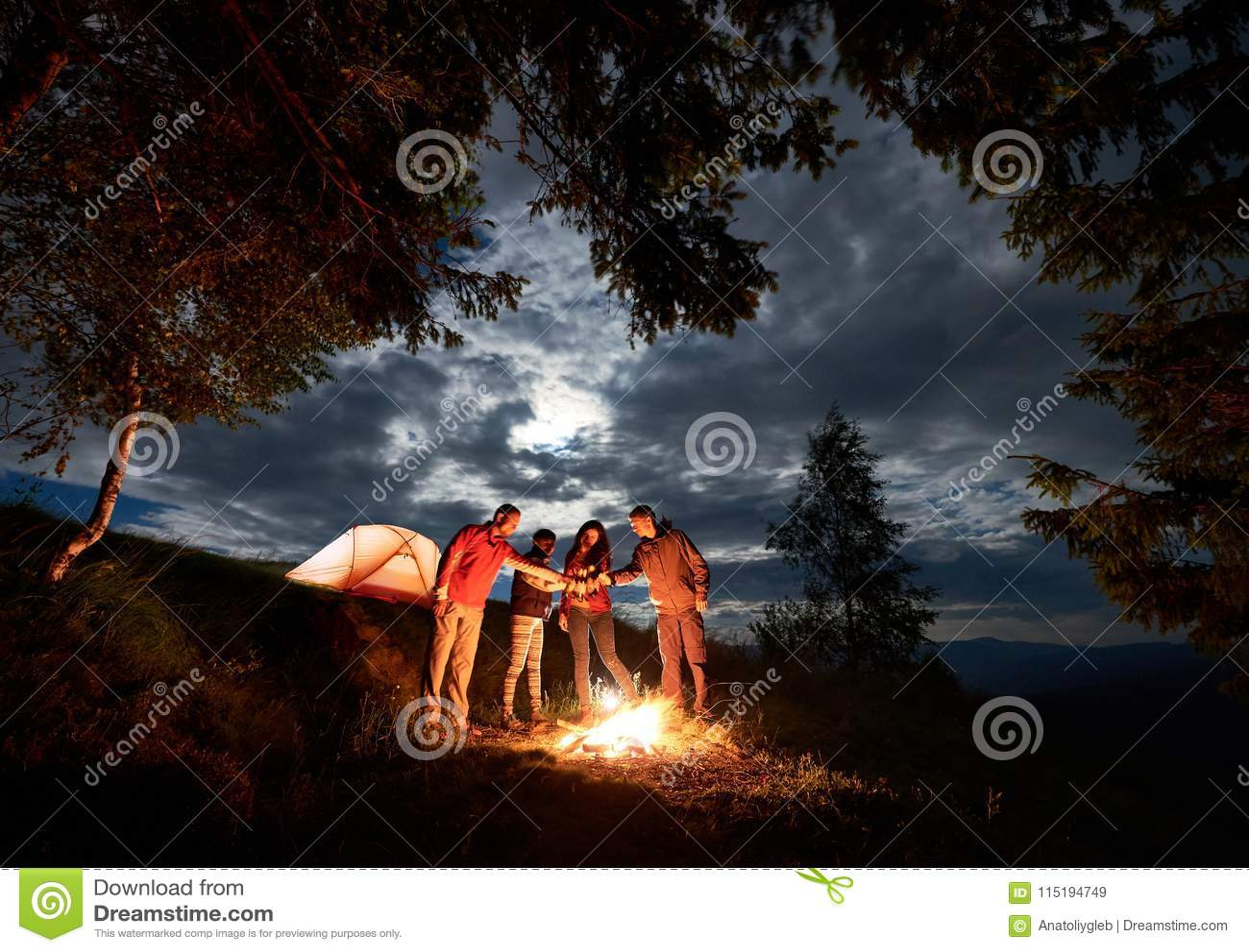 Ungdomarfirar ferie med öl vid branden nära tältet runt om träden under molnig himmel