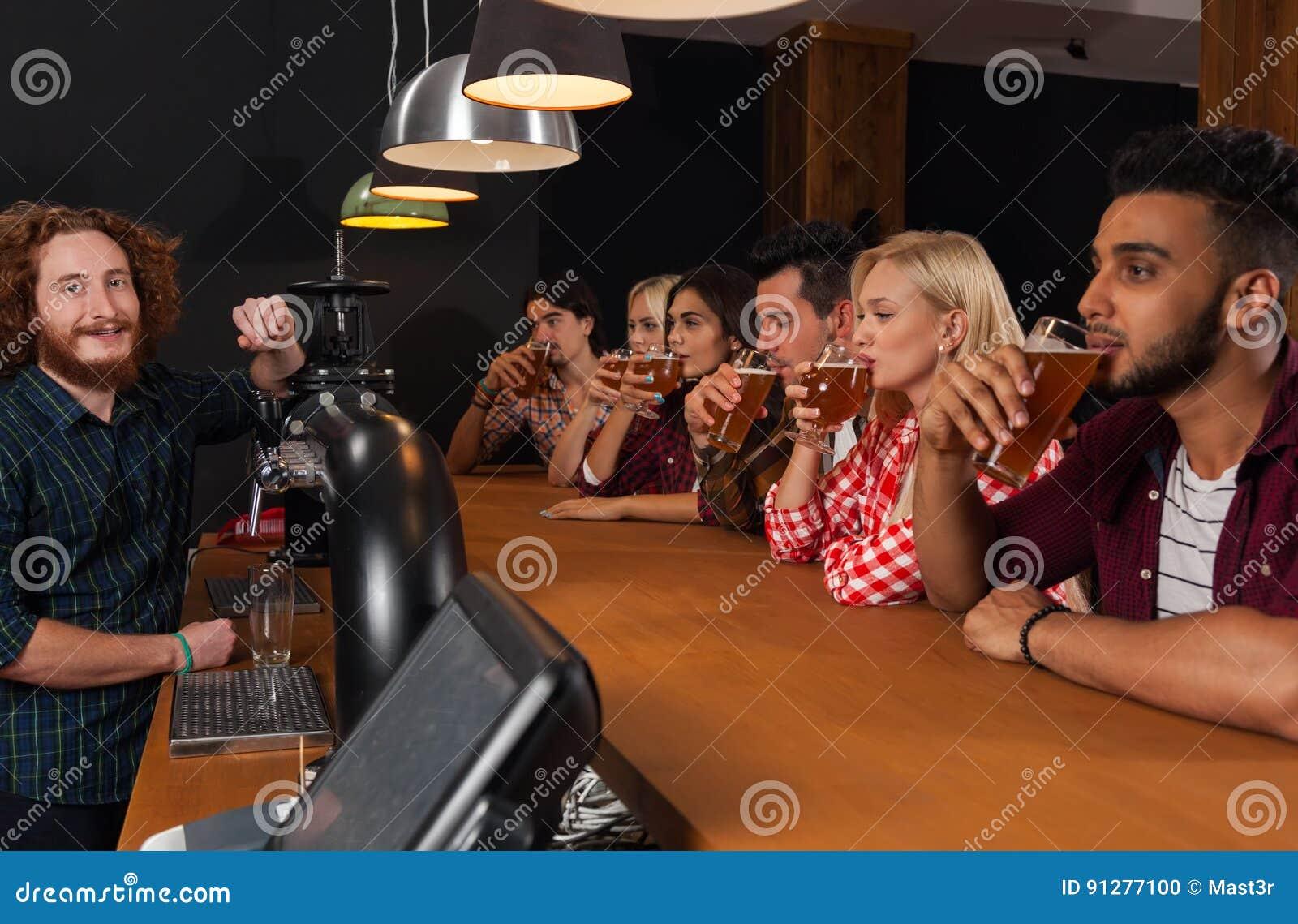 Ungdomargrupp i stången, bar för bartenderFriends Sitting At träräknare, drinköl