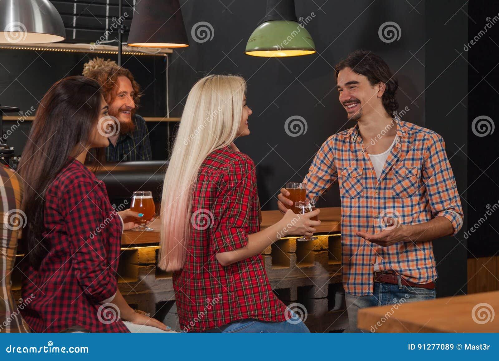 Ungdomargrupp i stången, vänner som sitter på träräknarebaren, drinköl