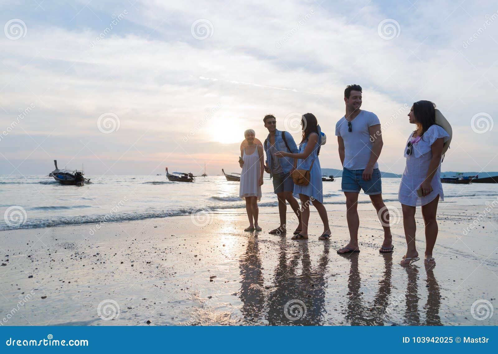 Ungdomargrupp på stranden på solnedgångsommarsemestern, vänner som går sjösidan