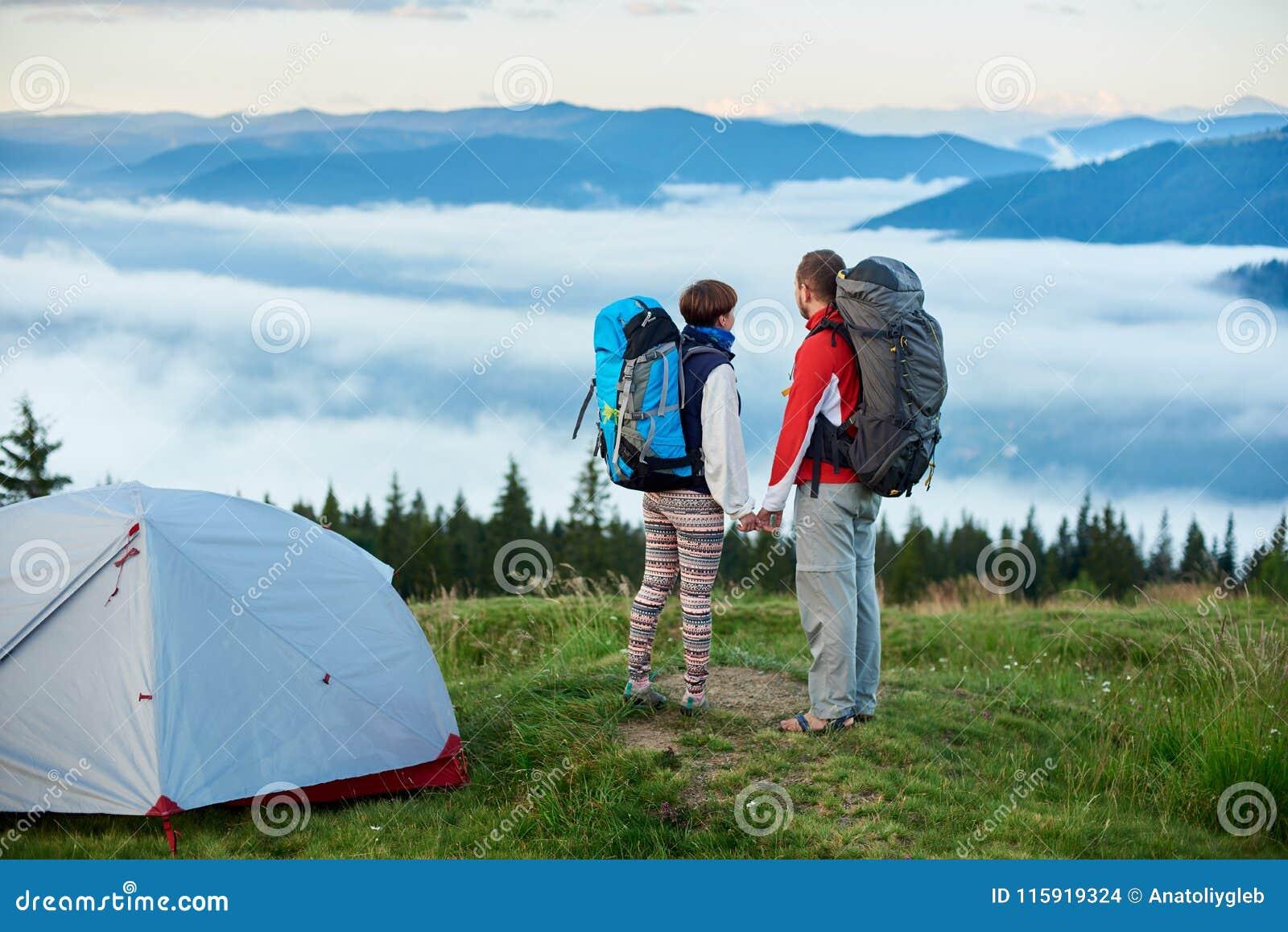Ungdomarmed near campa hållhänder och blick för ryggsäckar på berg