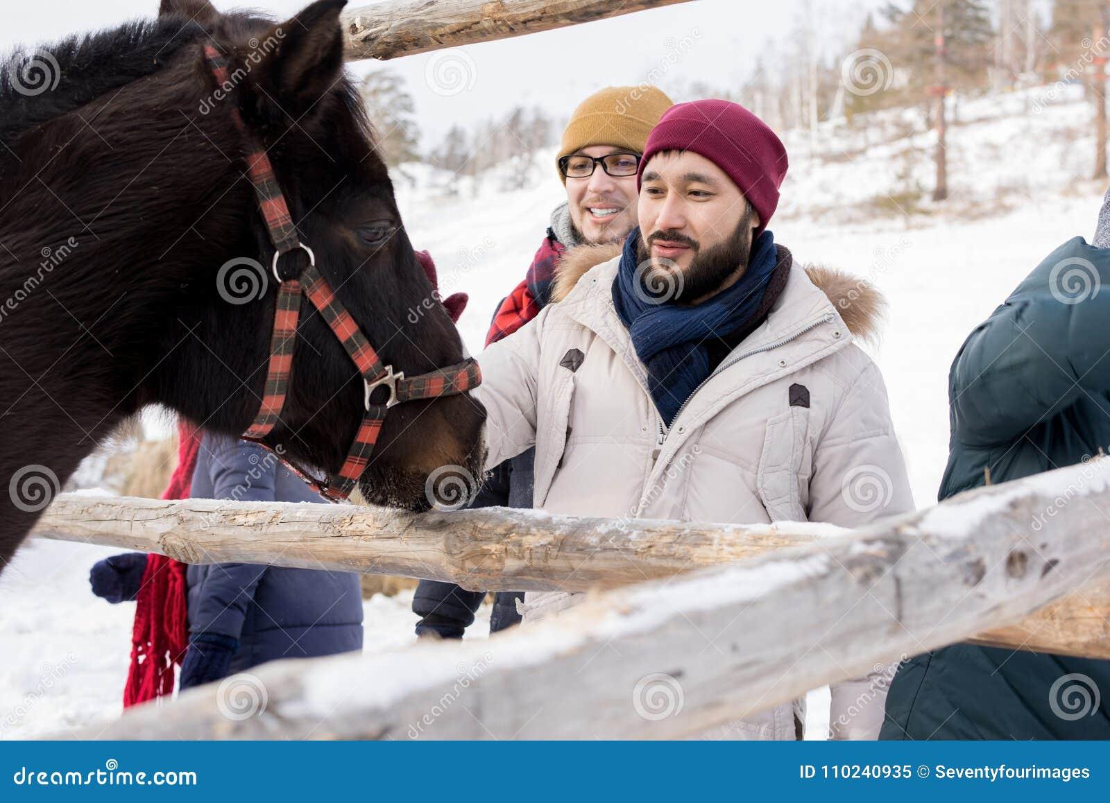 Ungdomarsom daltar hästar på ranch