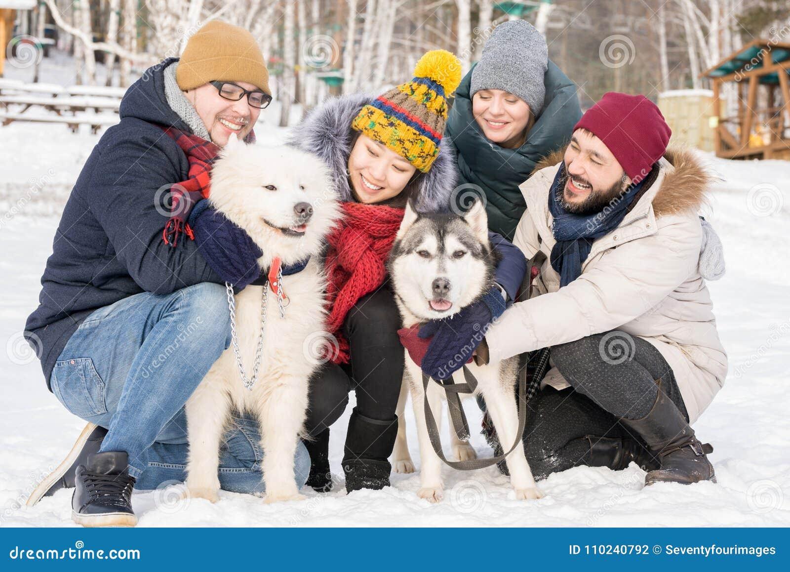 Ungdomarsom poserar med rashundar