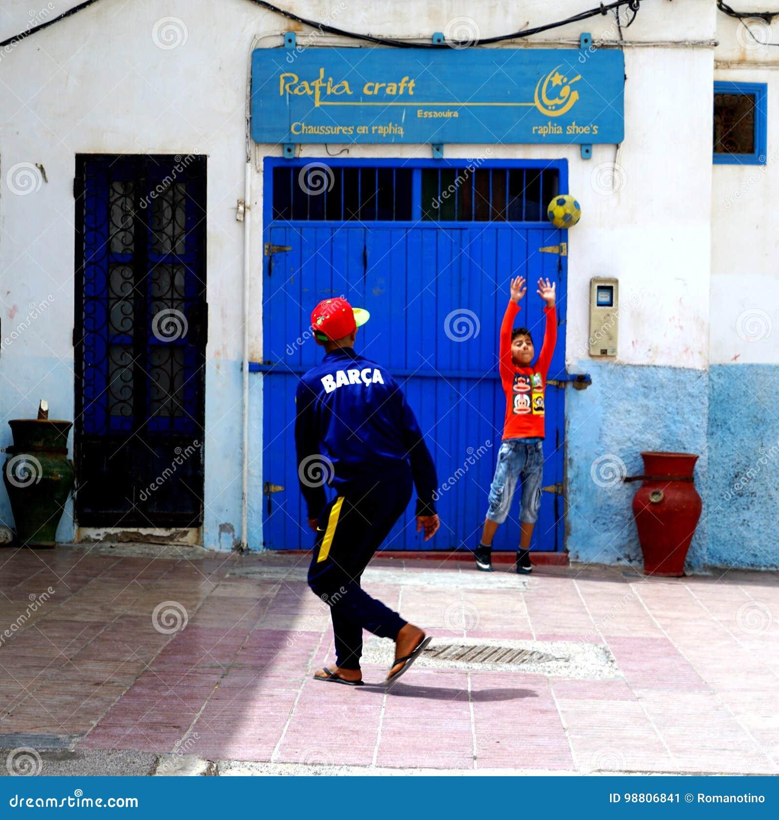 Ungdomarsom spelar fotboll i medinaen av Essaouira