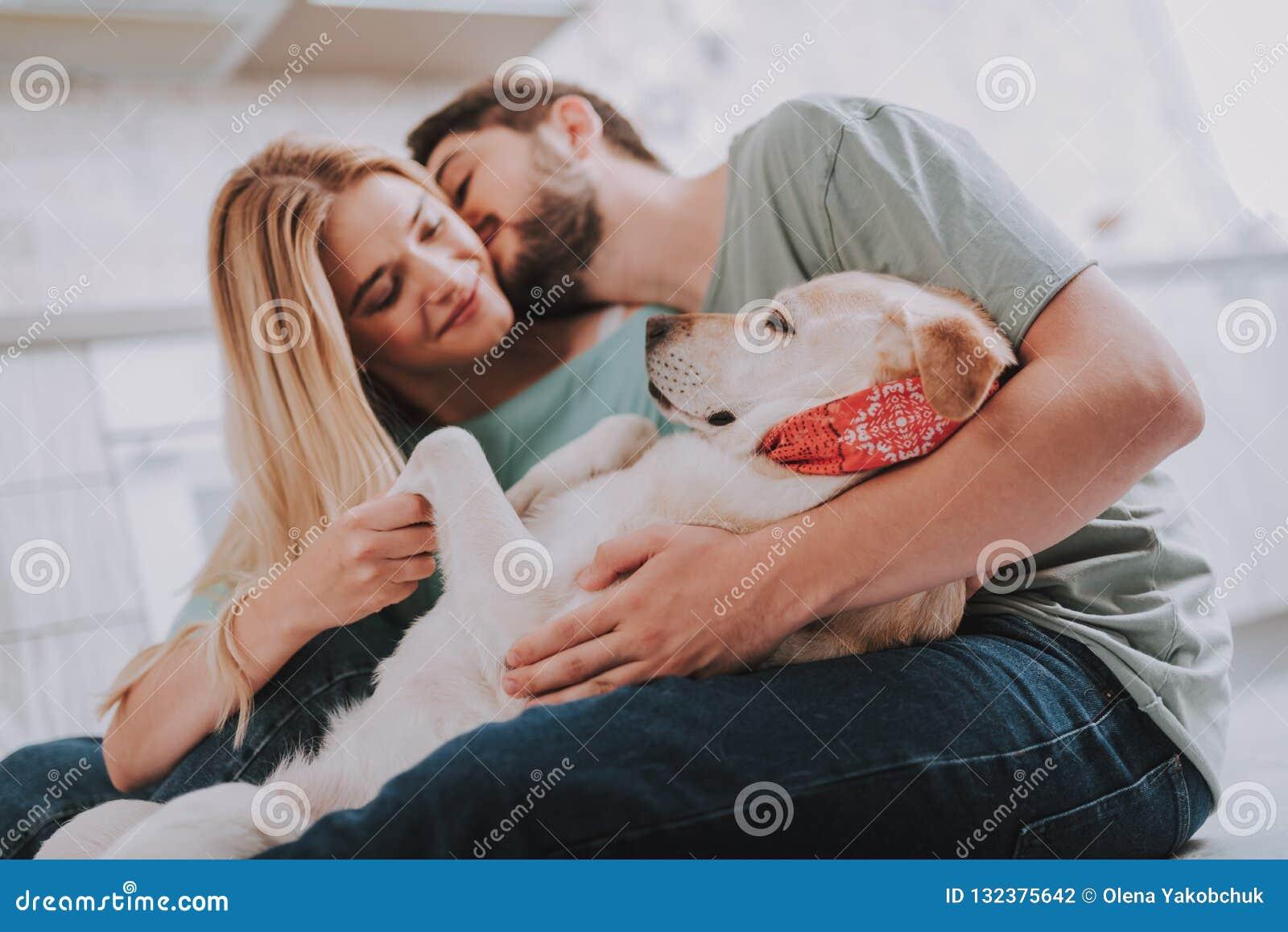 Ungdomliga kyssande par som omfamnar deras halkande hund
