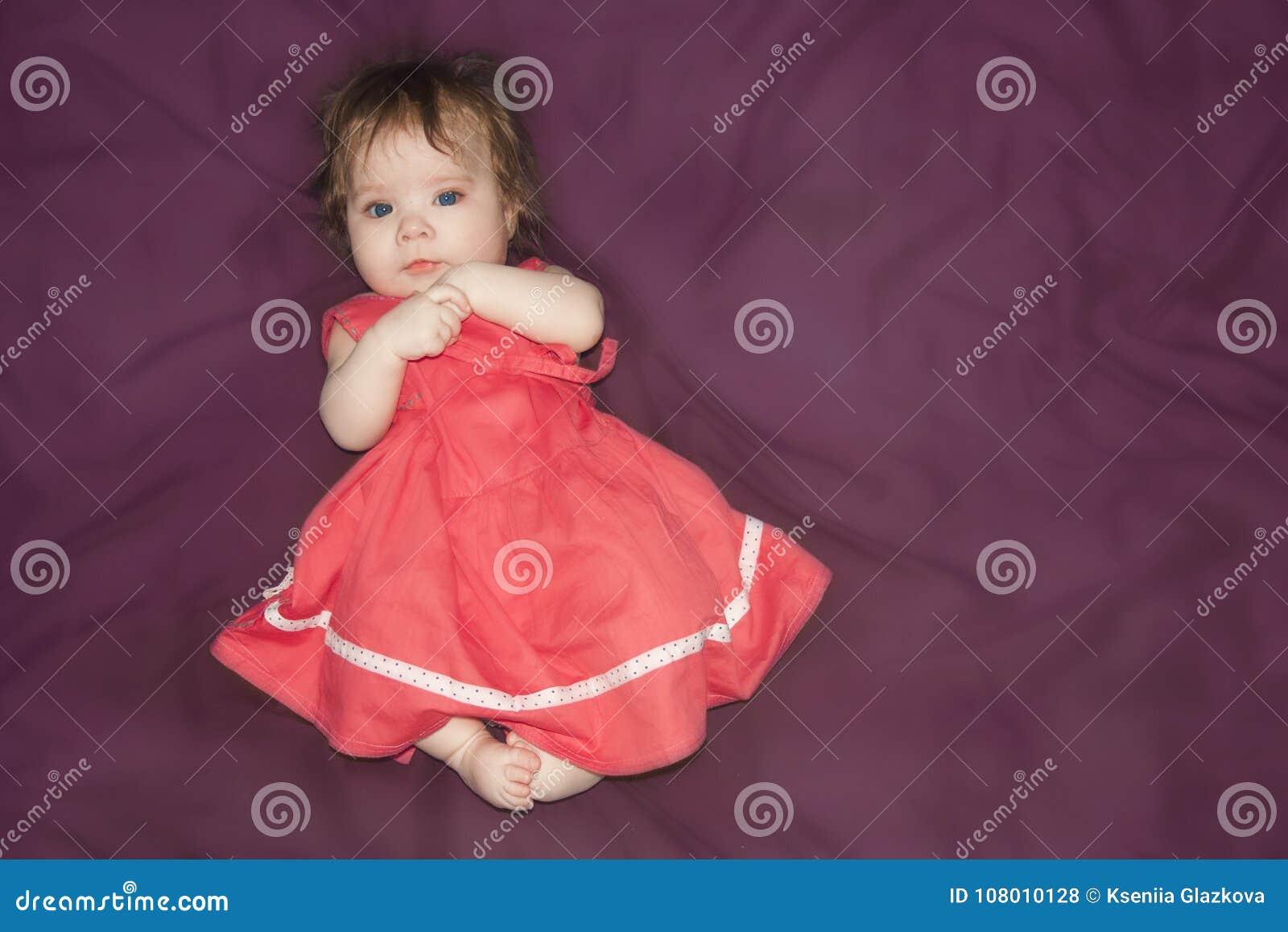 Unge flicka i en sniden klänning på en lila