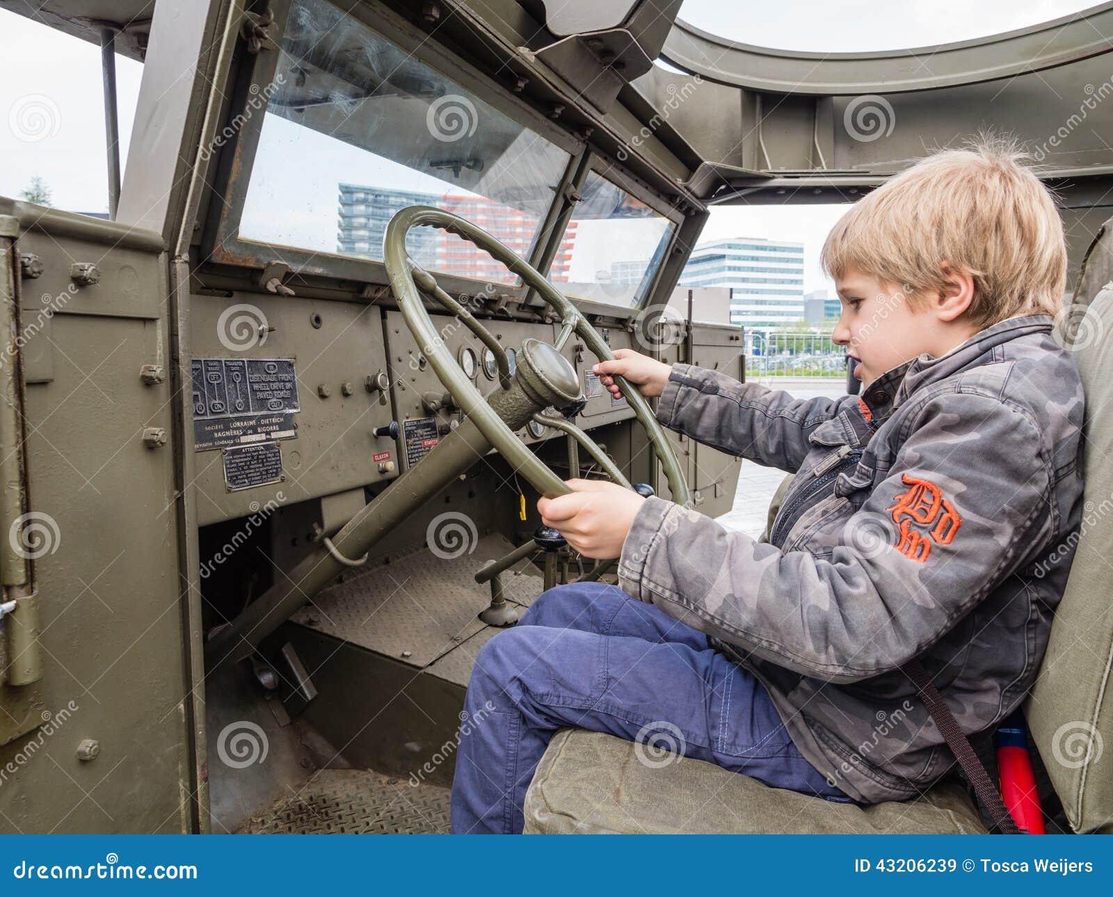 Download Unge På Hjulet Av En Militärfordon Redaktionell Fotografering för Bildbyråer - Bild av kamouflage, kriga: 43206239