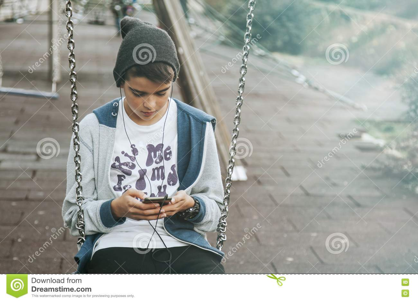 Unge som använder smartphonen på gunga