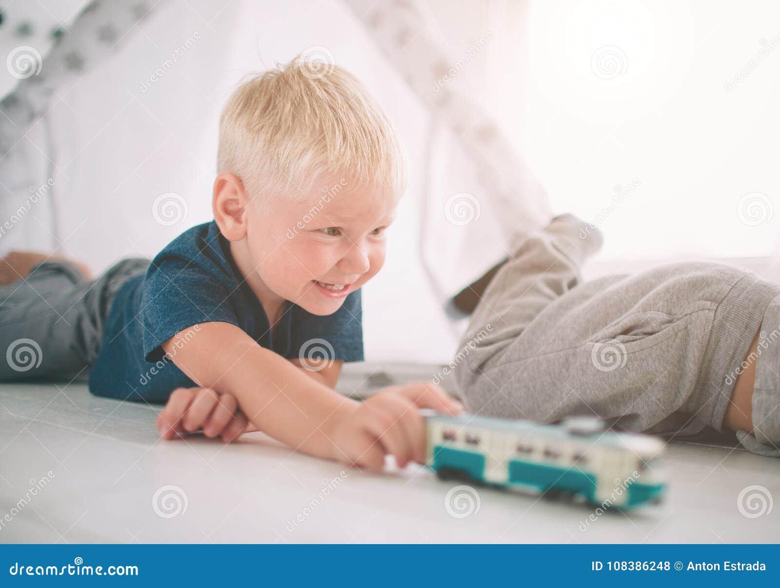 Ungebröder lägger på golvet Pojkar spelar i hem med leksakbilar hemma i morgonen tillfällig livsstil