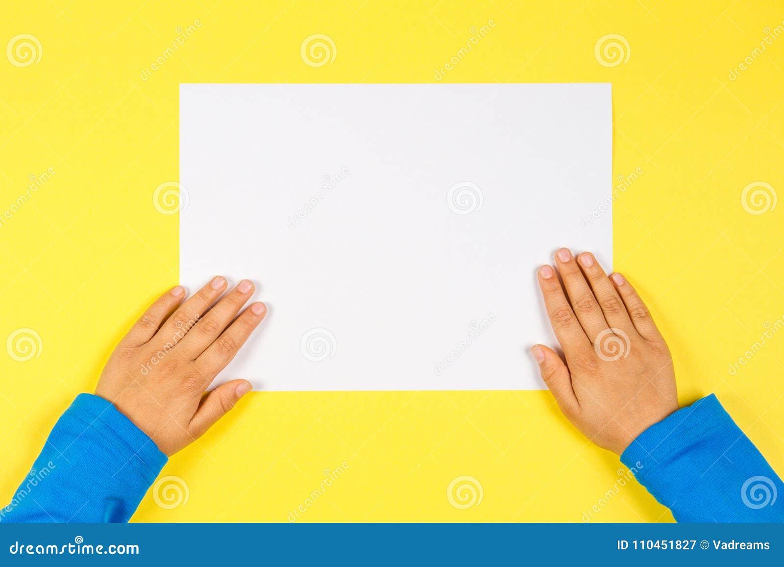 Ungehänder med det vita tomma pappers- kortet på gul bakgrund