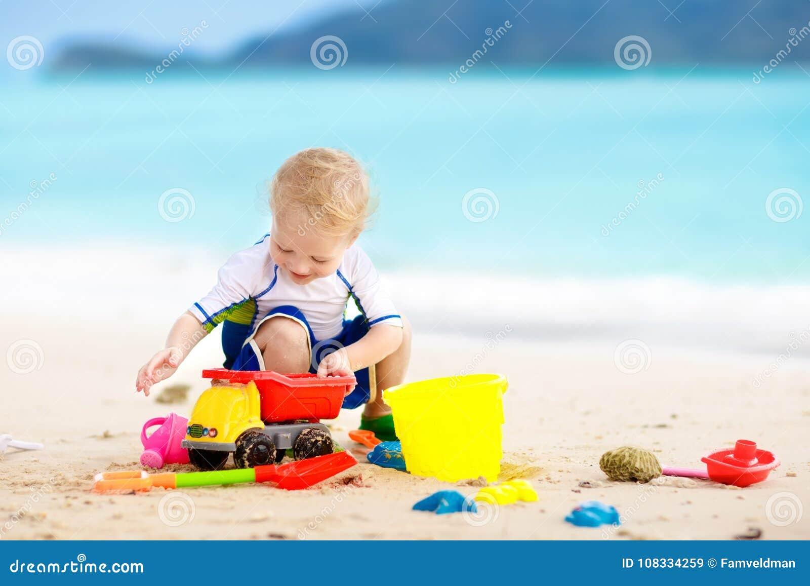 Ungelek på den tropiska stranden Sand- och vattenleksak