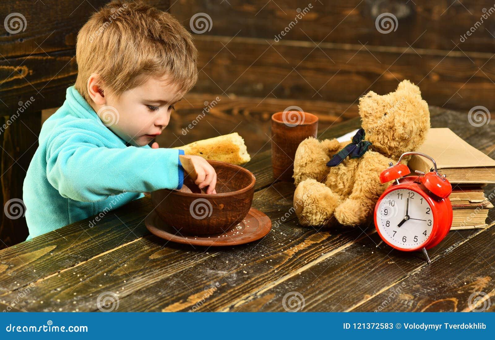 Ungen äter mat på trätabellen Ungen tycker om mål med leksakvännen Ungemeny Äta för liten unge äta vad dig