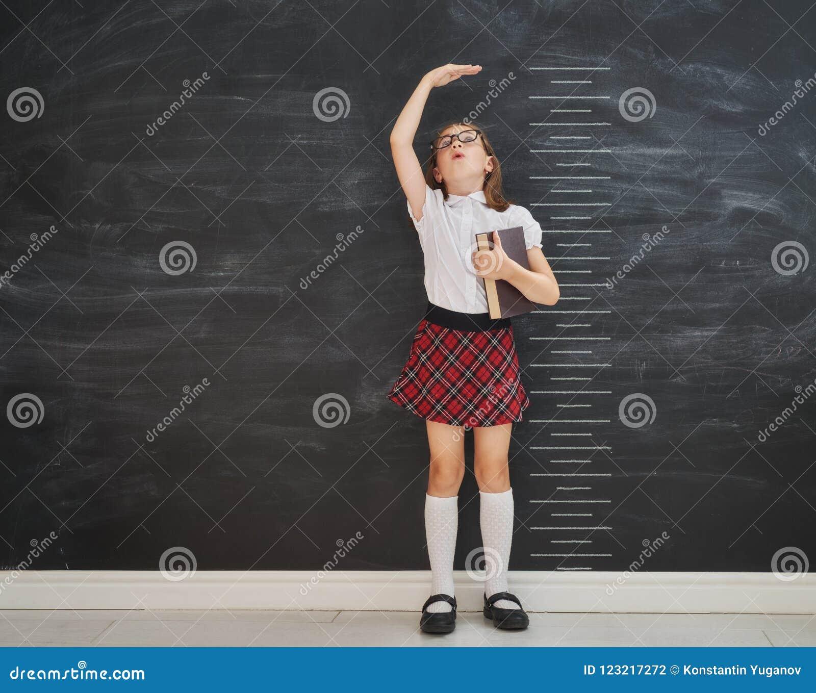Ungen mäter tillväxt på bakgrund av svart tavla