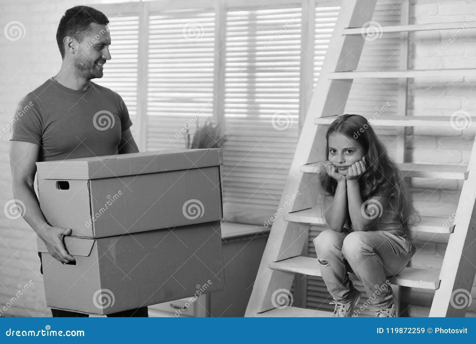 Ungen och grabben flyttar sig in eller flyttar sig ut Nytt hem- och familjbegrepp Dotter- och faderhållaskar och packar upp eller