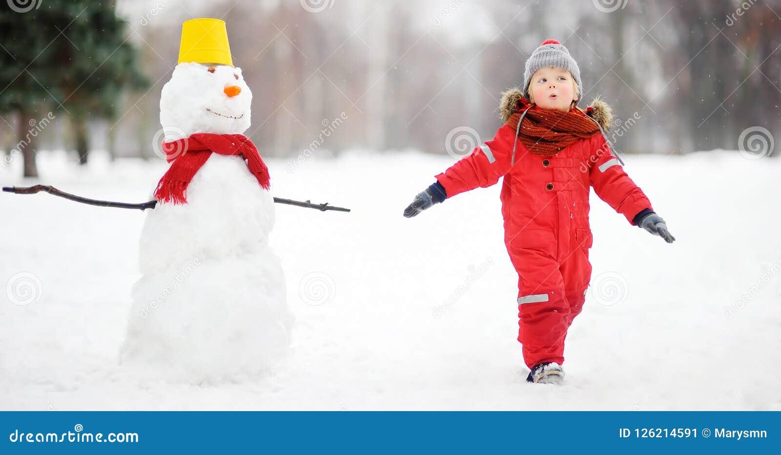 Ungen under promenad i en snöig vinter parkerar