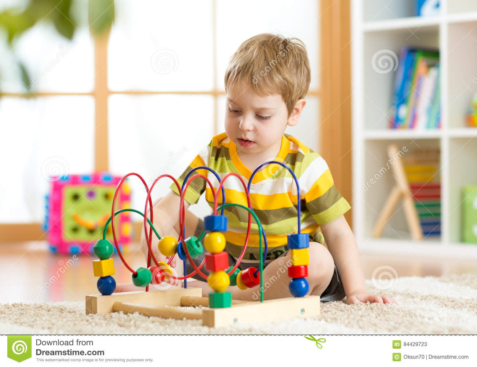 Ungepojken spelar med en mångfärgad logisk leksak i barnkammare