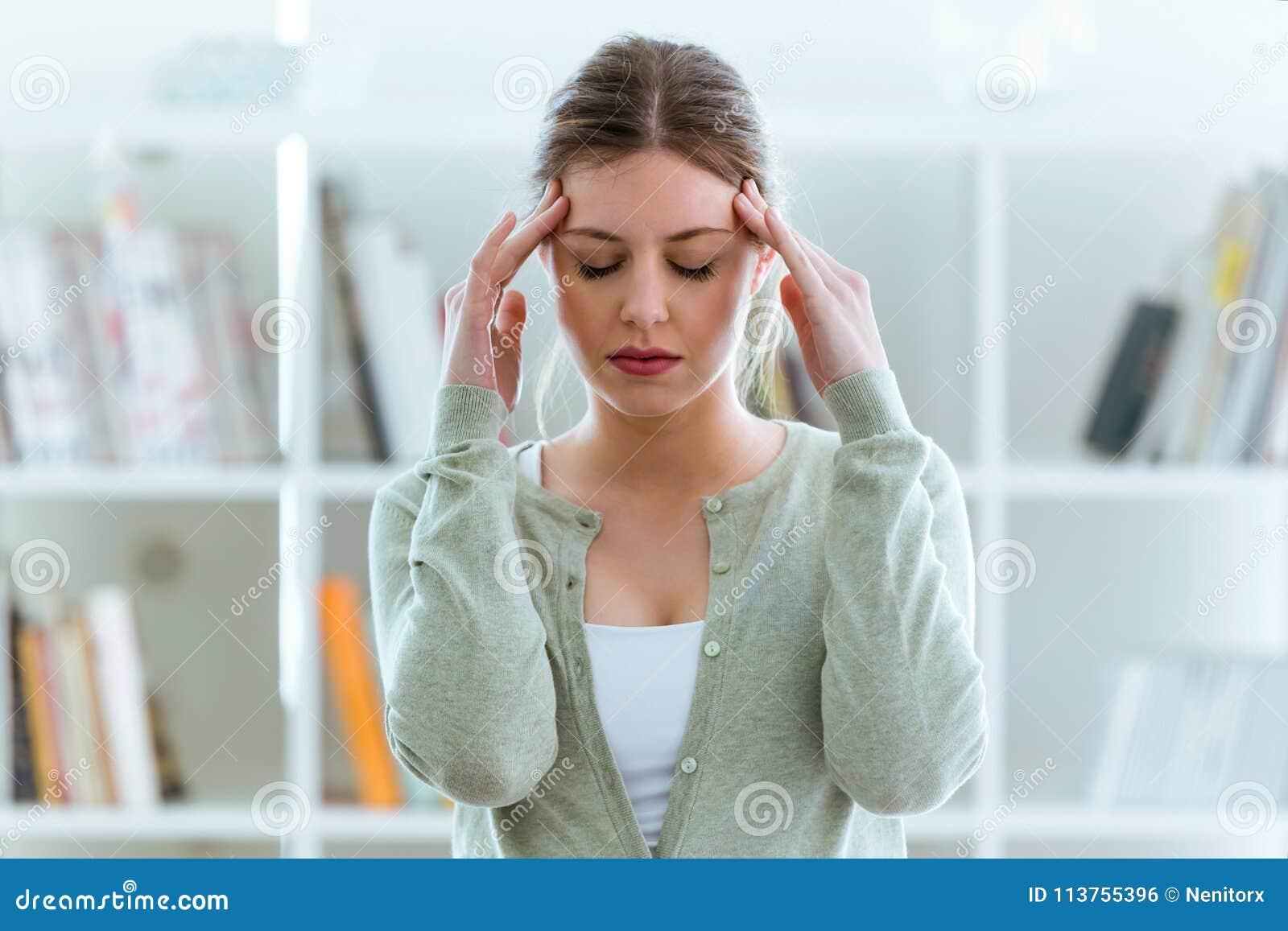 Ungesunde junge Frau mit den Kopfschmerzen, die zu Hause seinen Kopf berühren