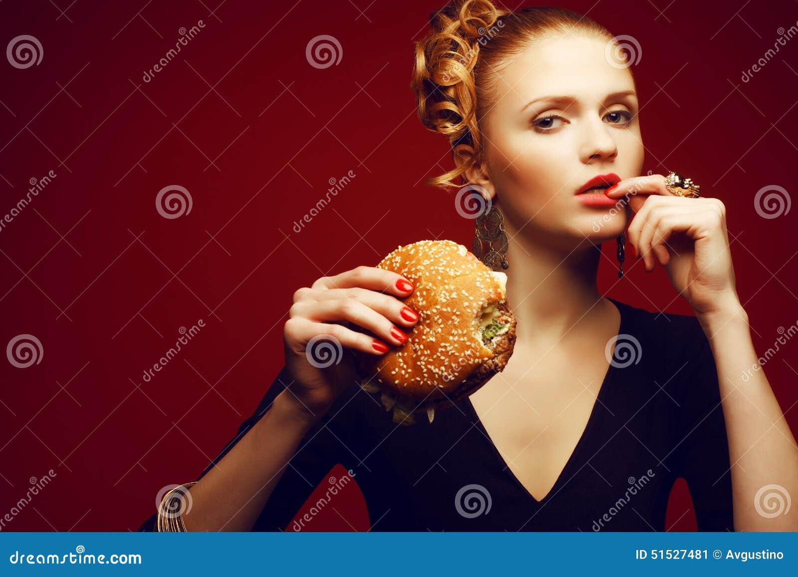 Ungesundes Essen Frittiertes Huhn- oder Fischburgersandwich mit Kopfsalat, Tomate, Käse und Gurke auf hölzernem Hintergrund Frau,