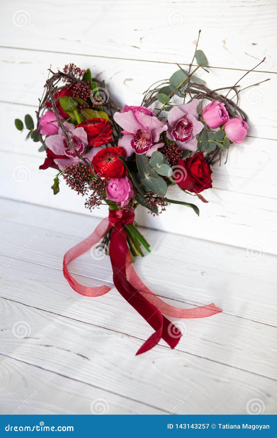 Ungewöhnlicher kreativer Blumenstrauß von Blumen in Form des Herzens auf weißem hölzernem Hintergrund 14. Februar Karte für Valen