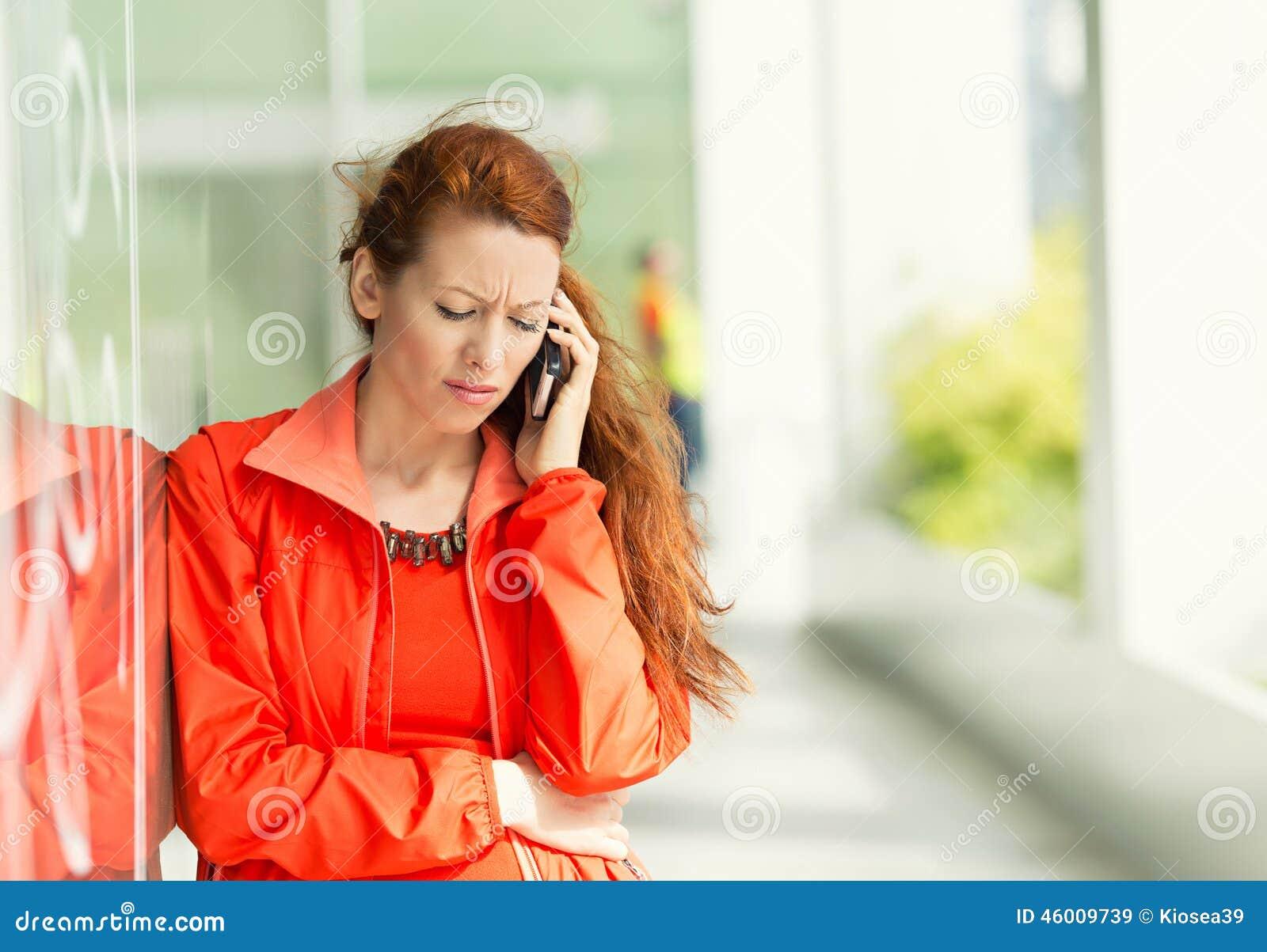 Unglückliche Frau an einem Telefon