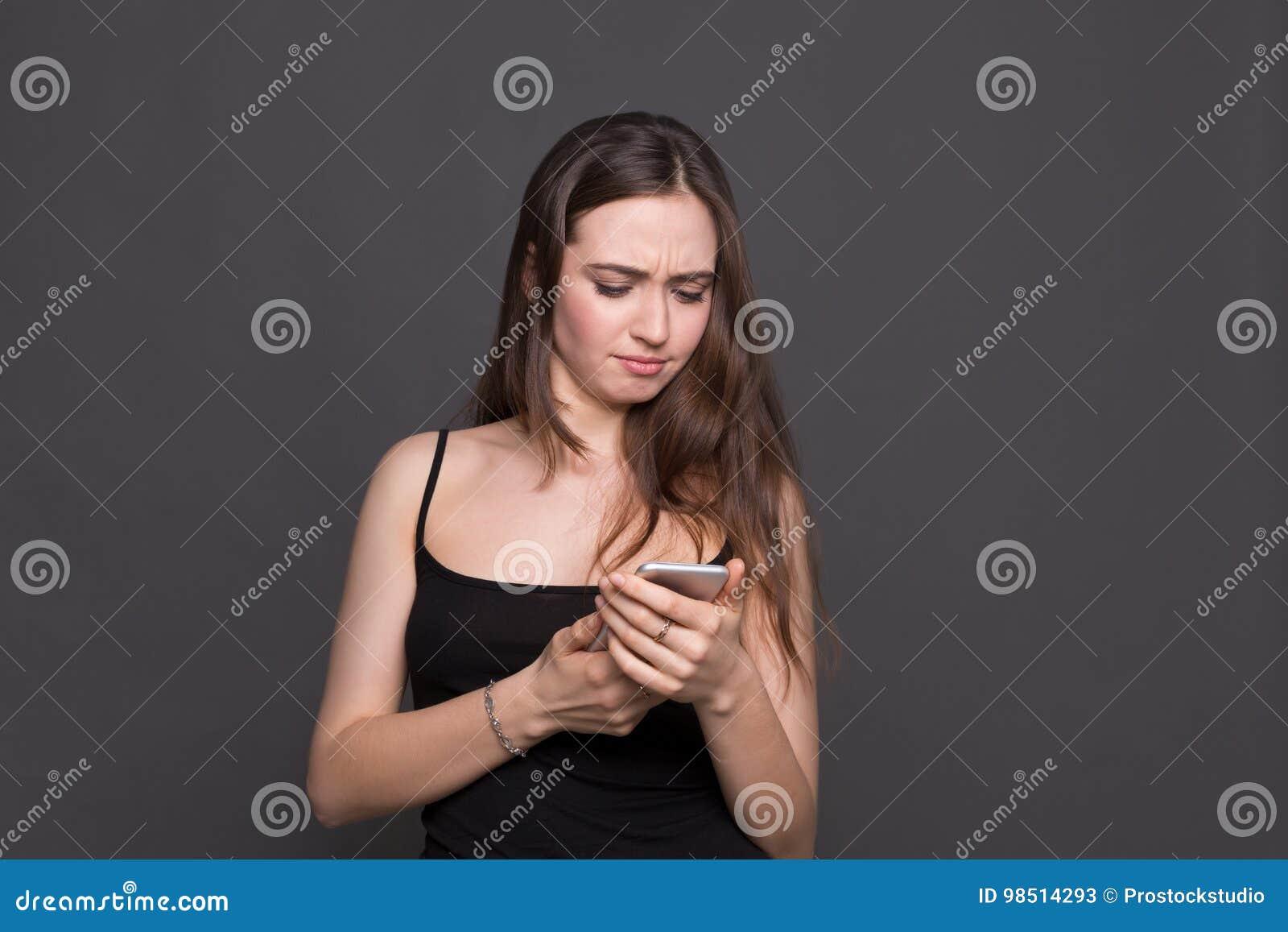 Unglückliche junge Frau, die Smartphoneporträt verwendet