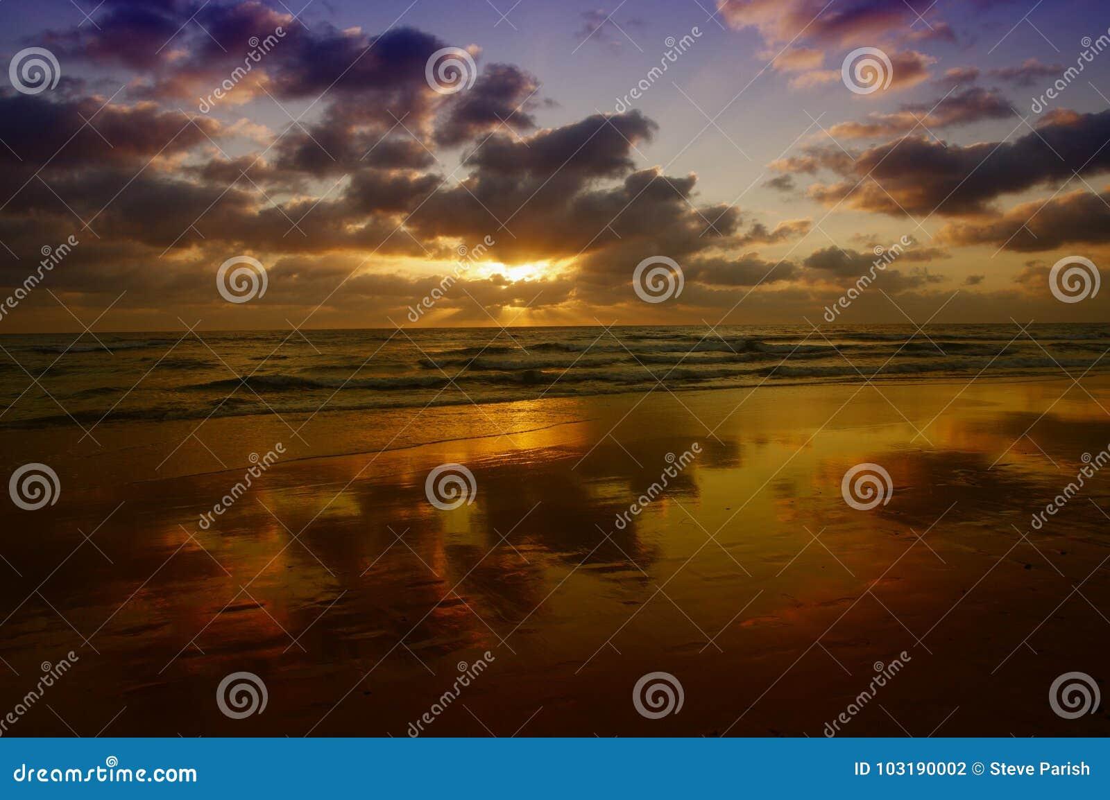 Unglaublicher Sonnenuntergang mit Wolken reflektierte sich im nassen Sand auf Strand
