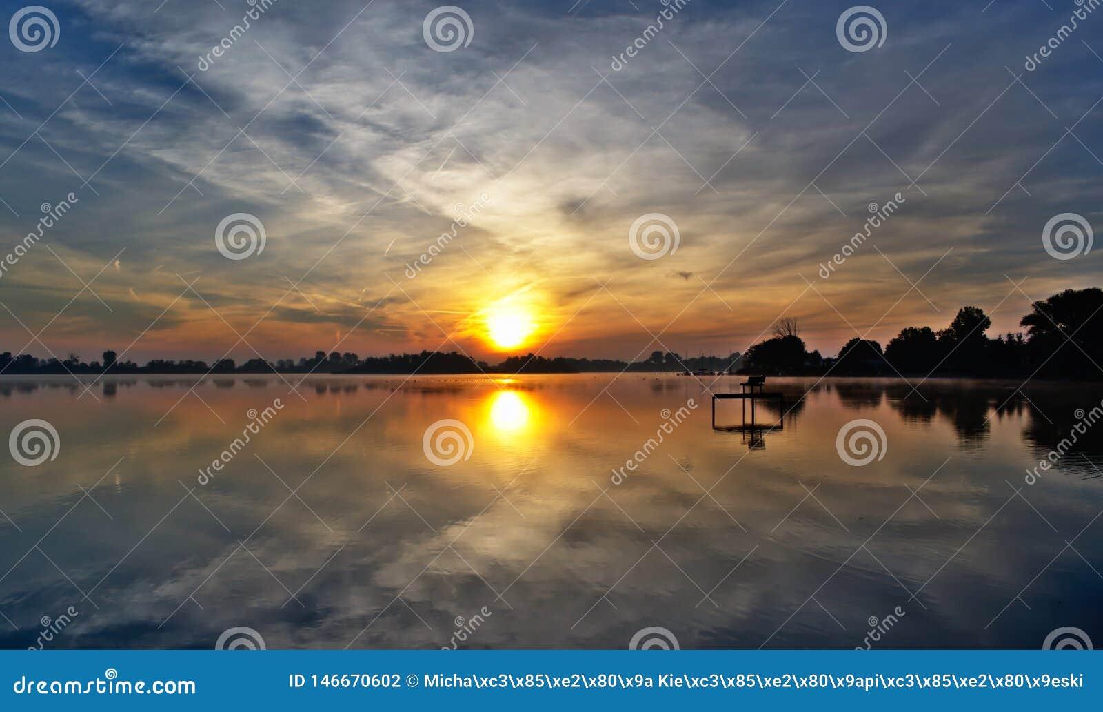 Unglaubliches Spiel des Lichtes im Himmel und im Wasser bei Sonnenaufgang über dem See