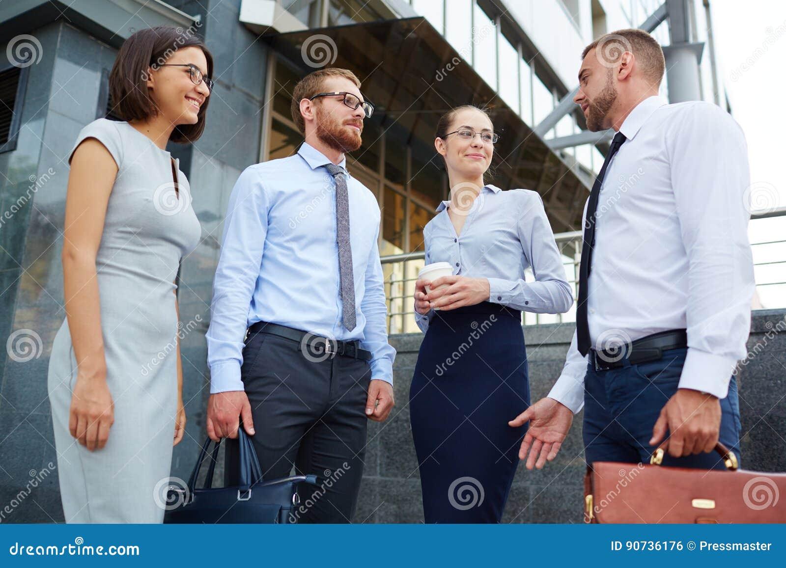 Ungt affärsfolk utanför kontorsbyggnad