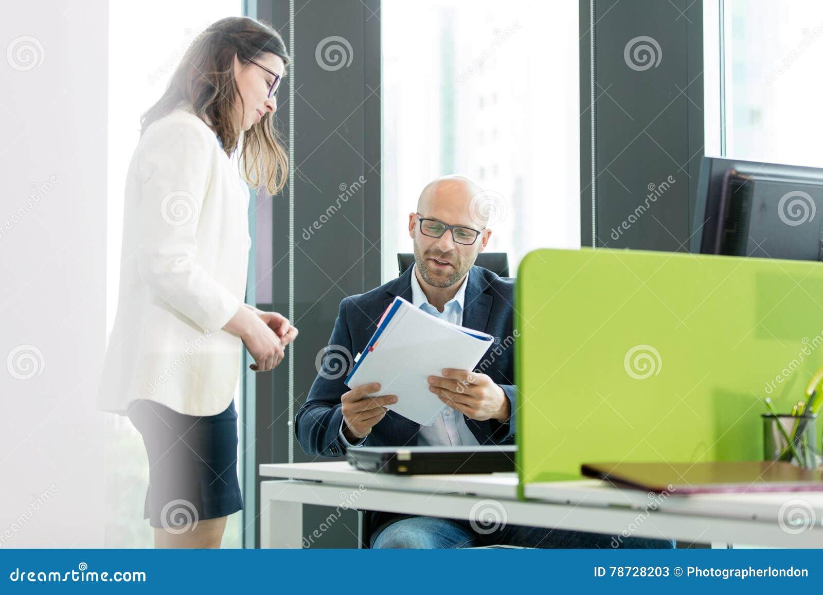 Ungt affärskvinnaanseende vid affärsmanläseboken på kontoret