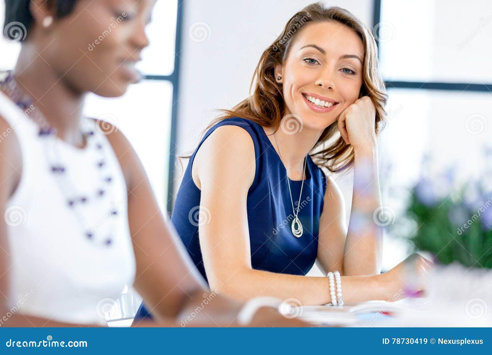Ungt affärskvinnasammanträde på skrivbordet och arbete