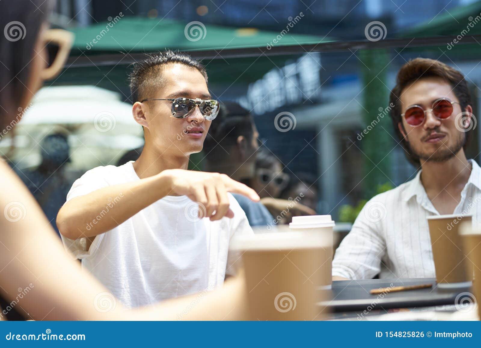 Ungt asiatiskt folk som kopplar av i coffee shop