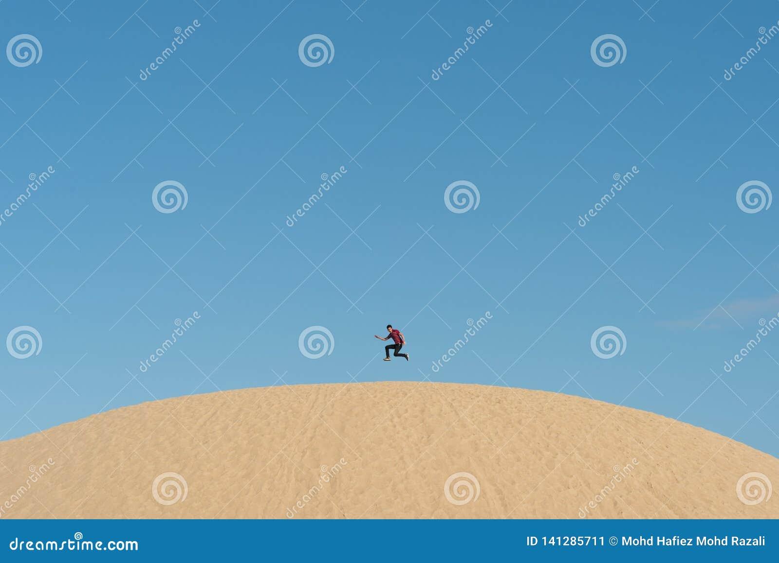 Ungt asiatiskt hoppa för man som är högt på dyn för en sand mot klar blå himmel