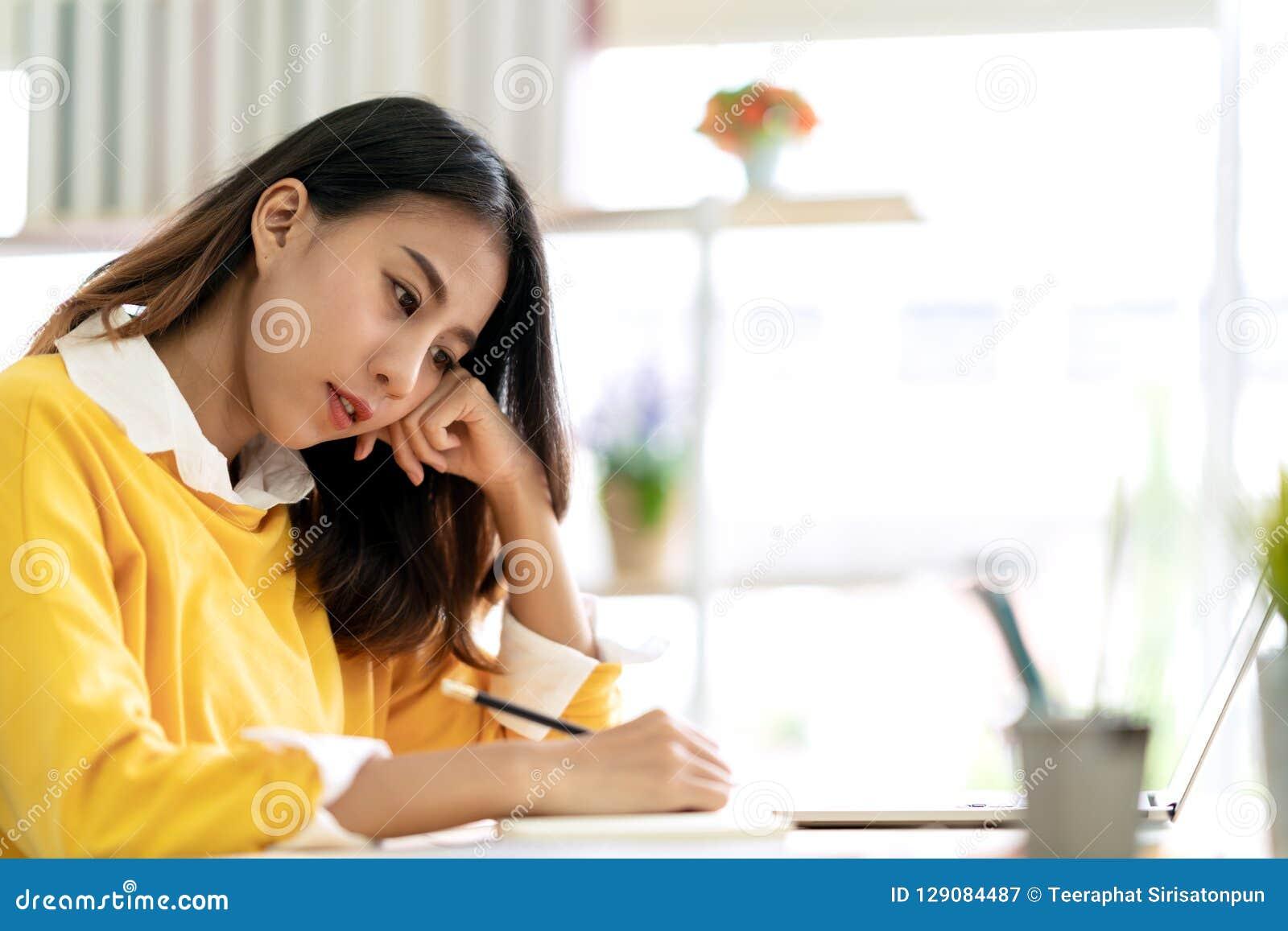 Ungt attraktivt asiatiskt sammanträde för den kvinnliga studenten på tabellen som tänker och skriver tidskriften vid skriften för
