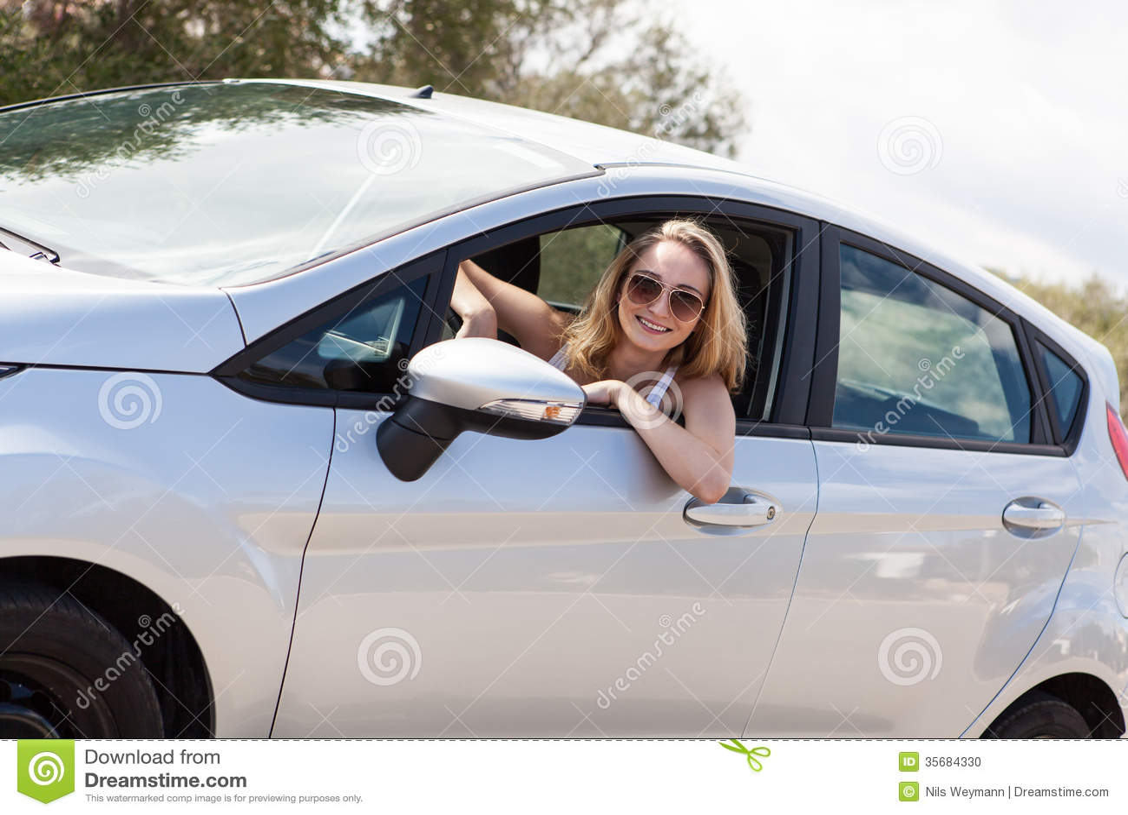 Ungt attraktivt lyckligt kvinnasammanträde i bilsommartid