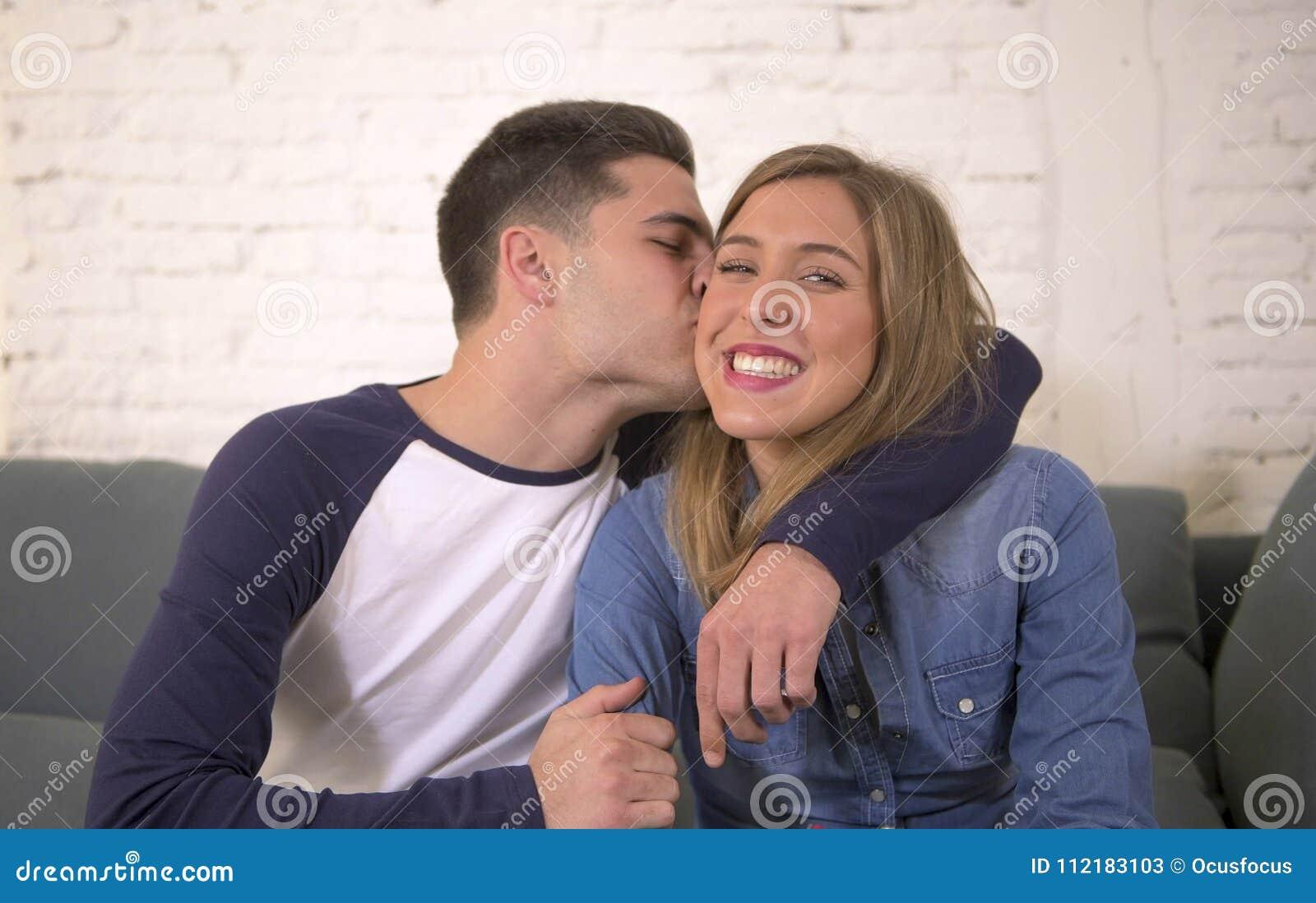 Ungt attraktivt lyckligt och romantiskt le för soffa för anbud för parpojkvän- och flickvänomfamning som hemmastatt är skämtsamt