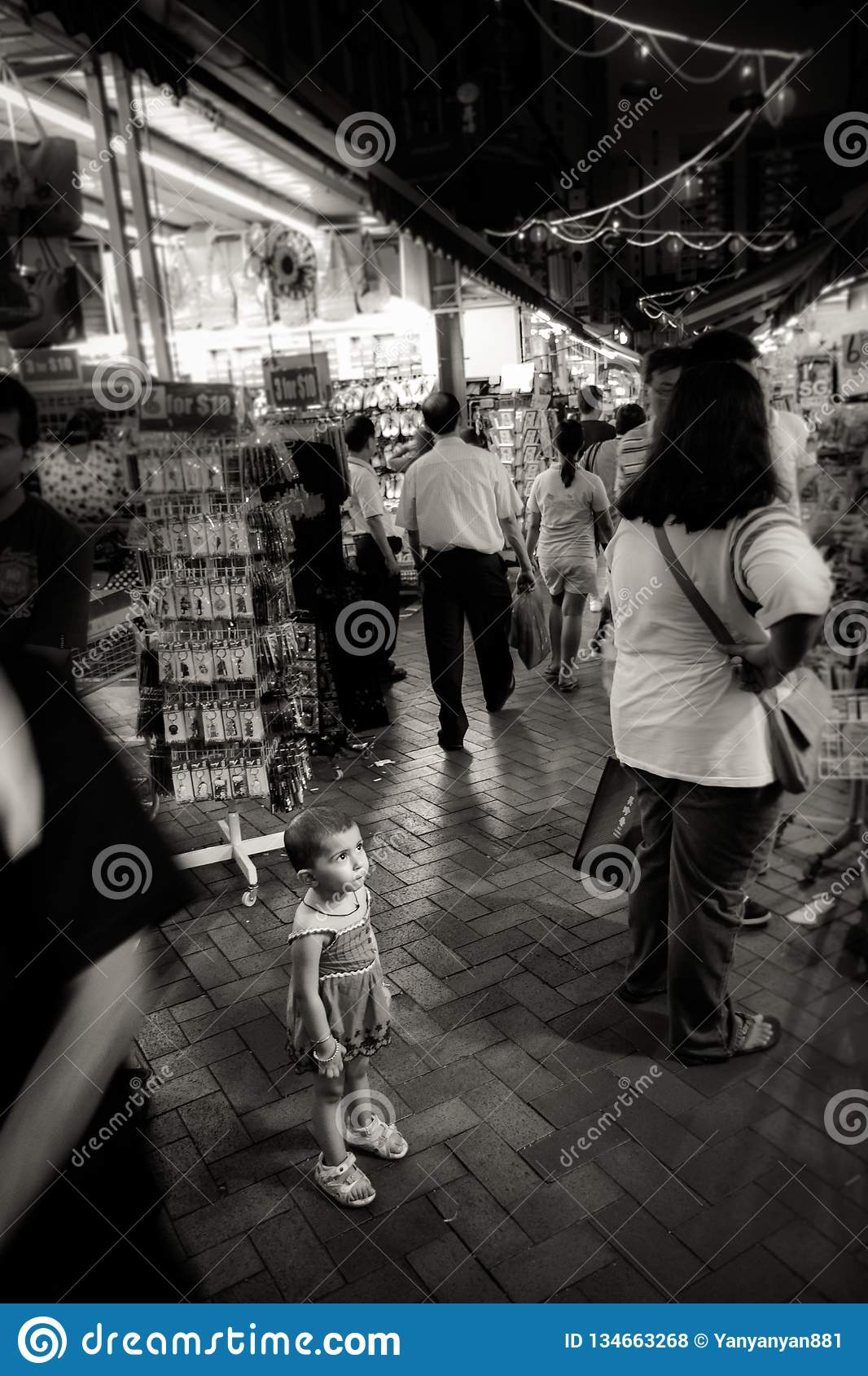 Ungt barnblickar förlorade i den fullsatta chinatown gatan, Singapore