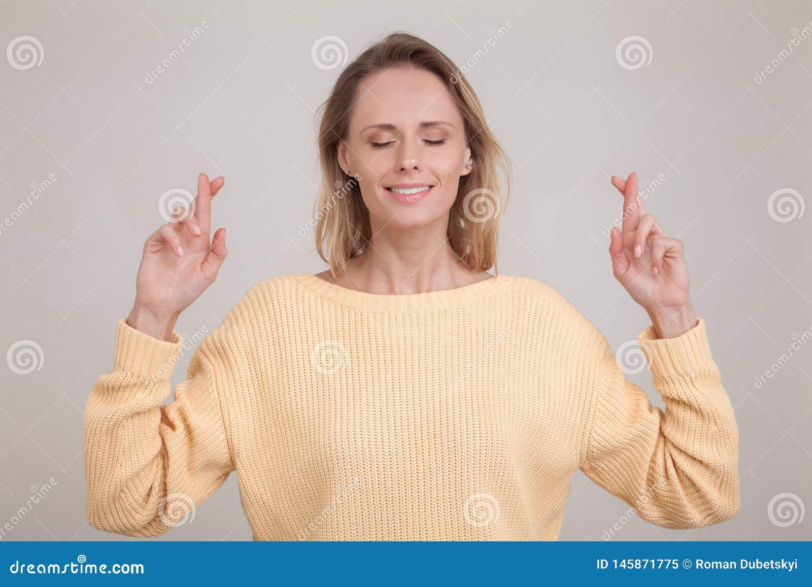 Ungt caucasian blont kvinnligt bokslut henne ?gon som korsar fingrar med hopp som f?rutser viktig nyheterna b?rande gul tr?ja