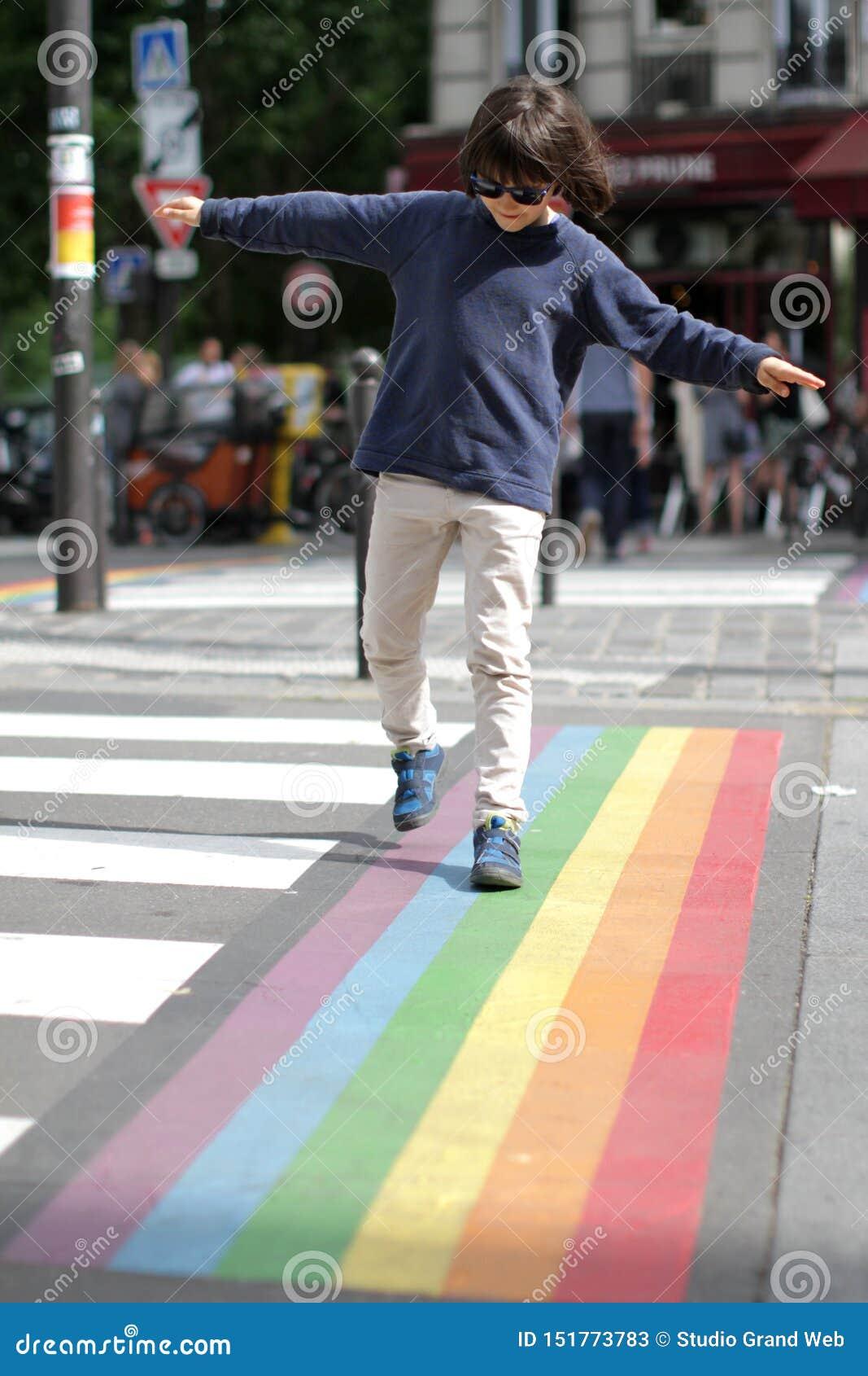 Ungt försiktigt barn som korsar gatan med gyckel, stadsbakgrund